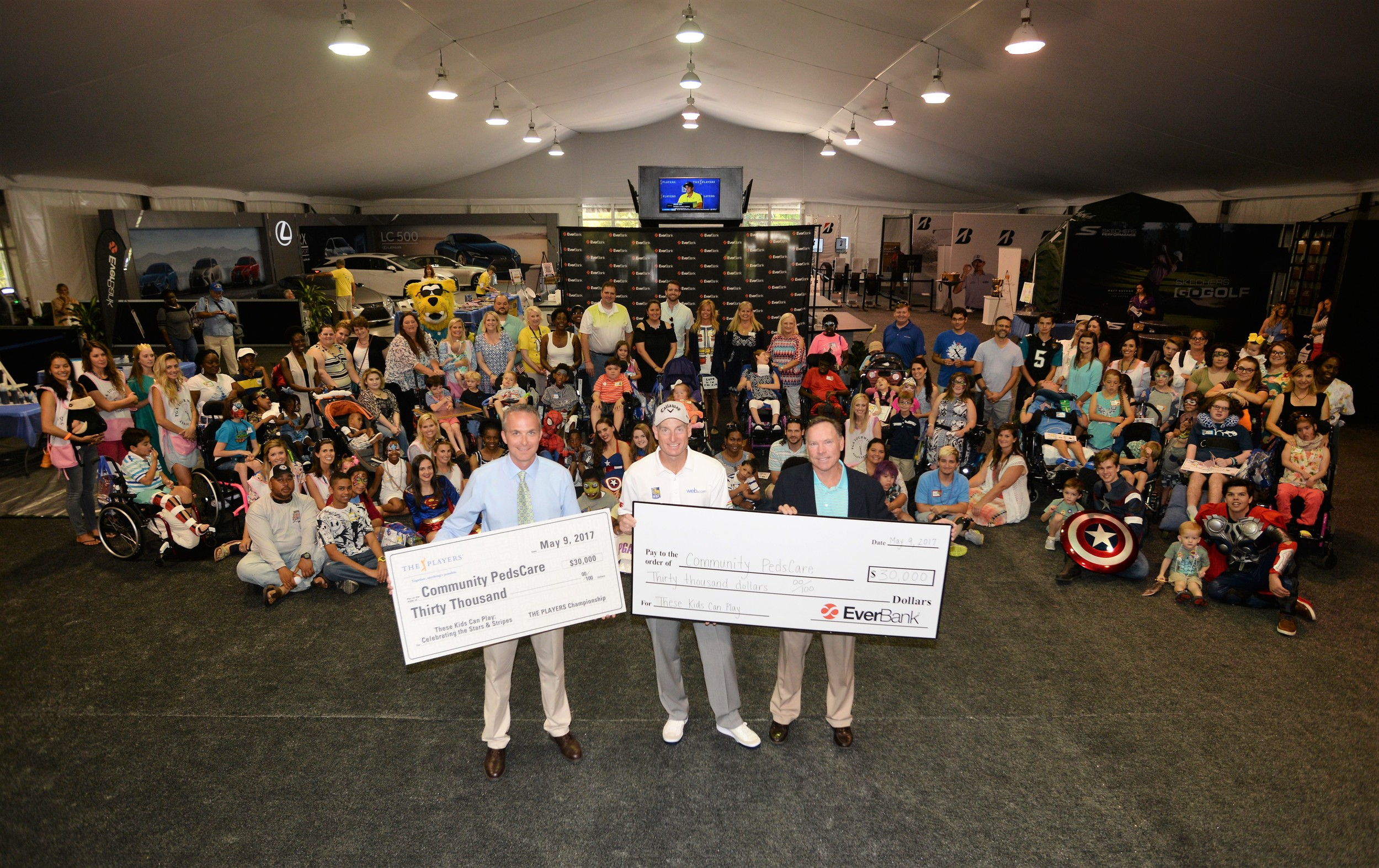THE PLAYERS Championship Executive Director Jared Rice, PGA Tour player Jim Furyk and Everbank President of North Florida Banking Curt Cunkle display the donations to Community PedsCare.