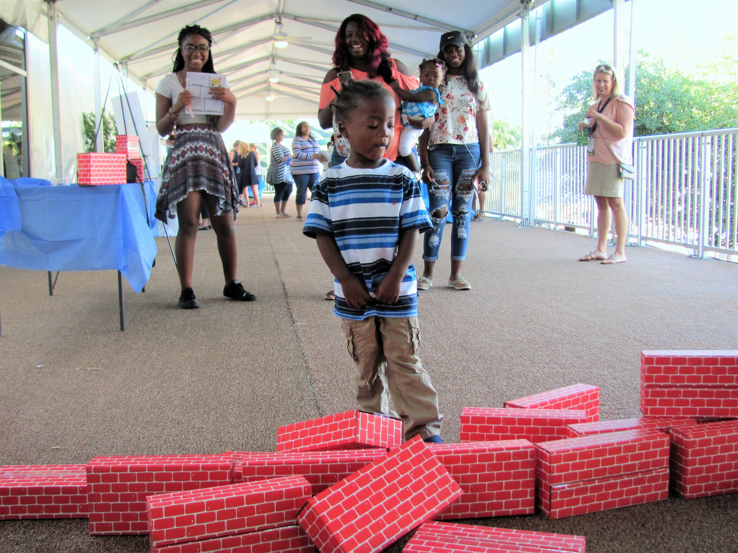 One of the children at the event kicks over a stack of blocks.