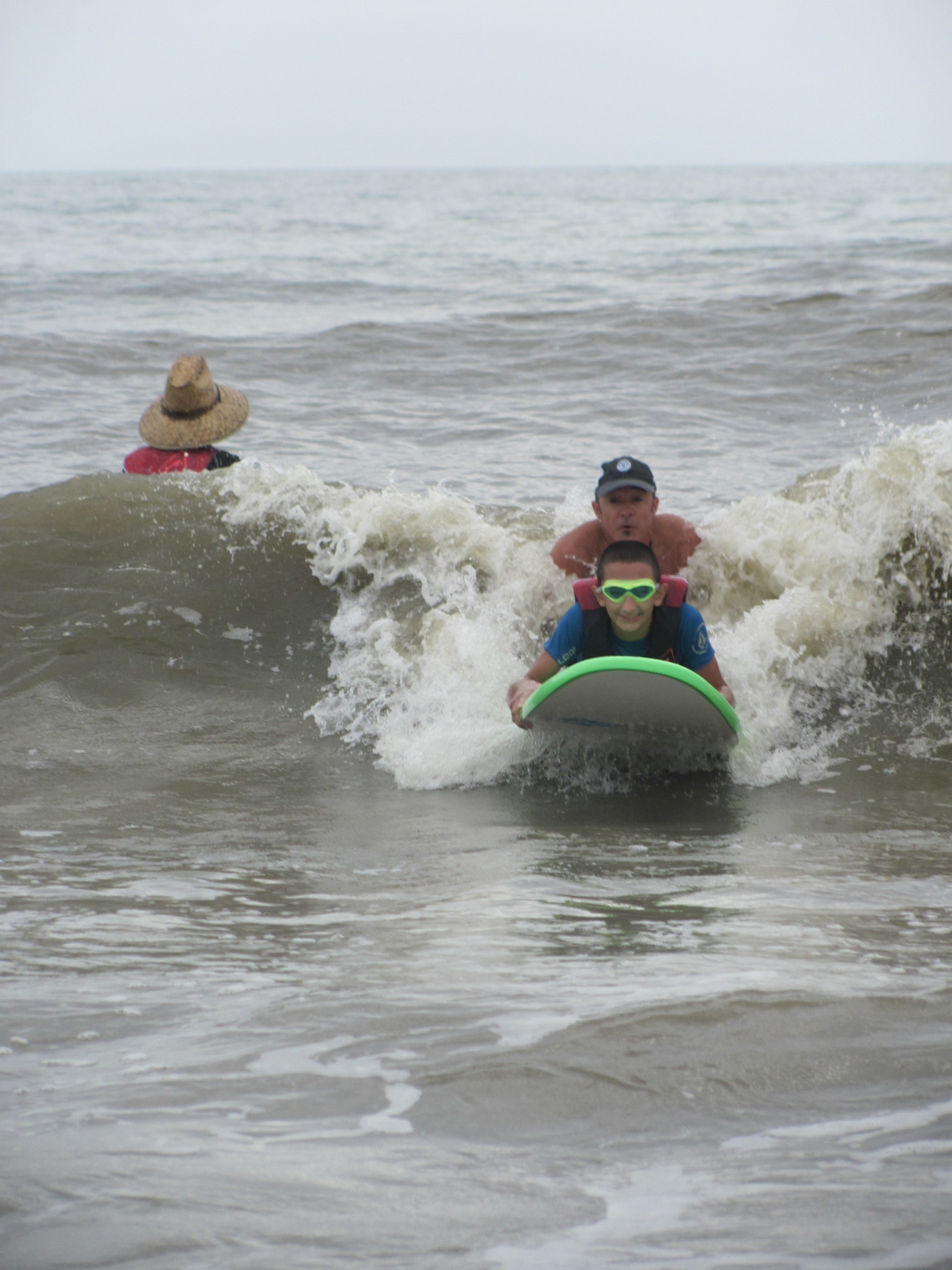 A camper smiles as he rides a wave toward the shore.