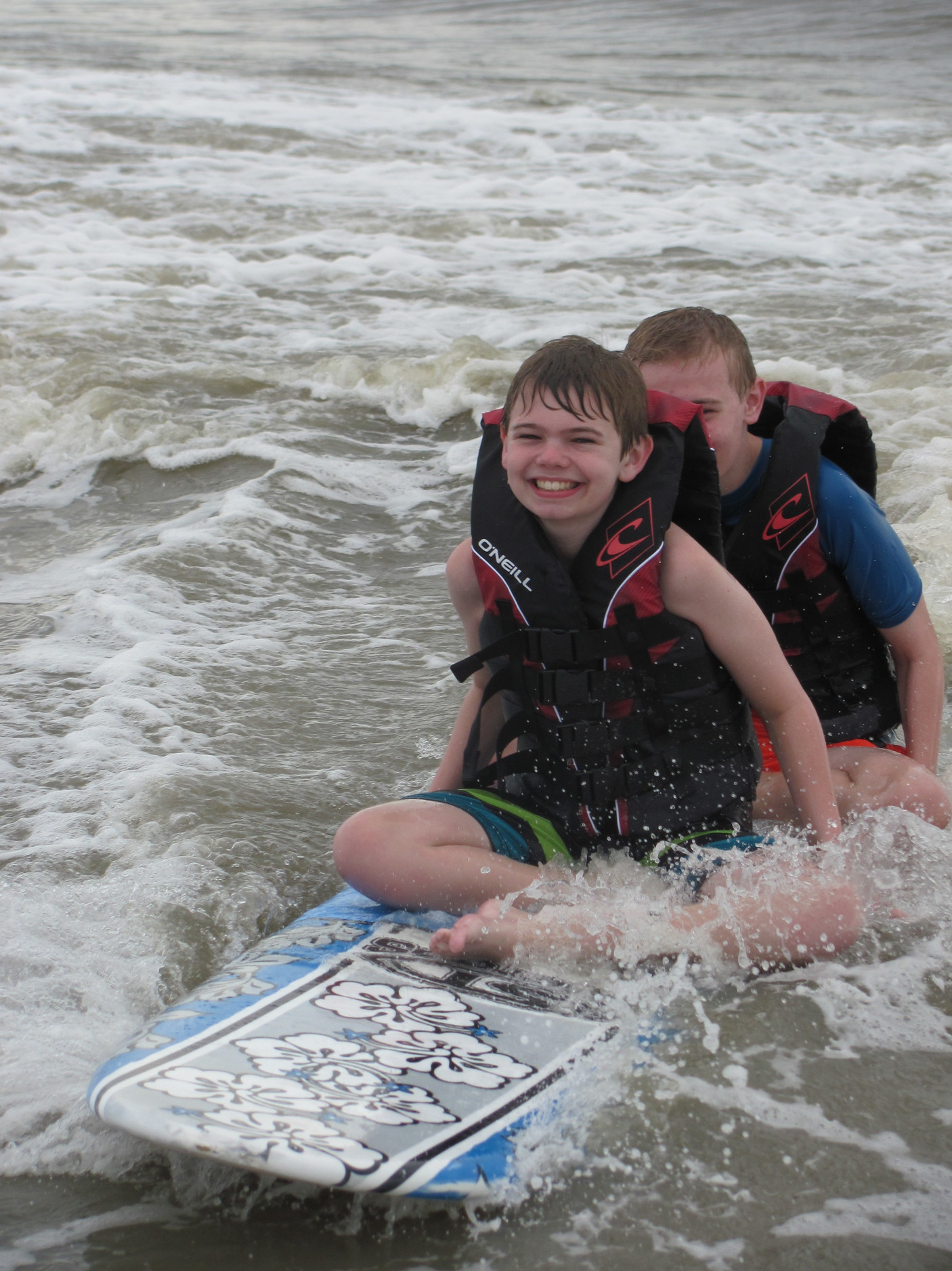Two campers ride tandem on their surf board.