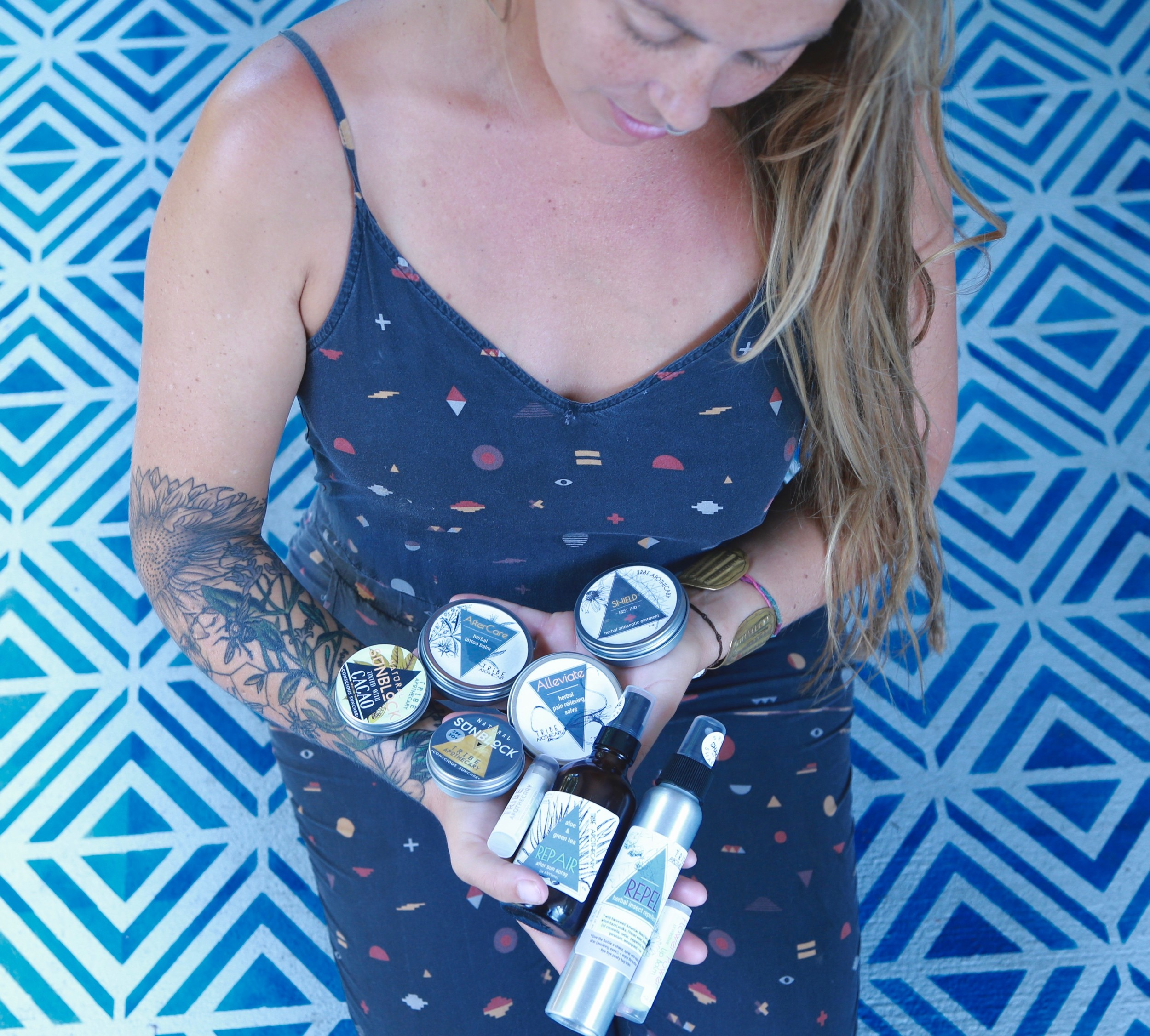 Tribe Apothecary owner Lauren Estes displays the various sunscreen and skin care products that her business sells.