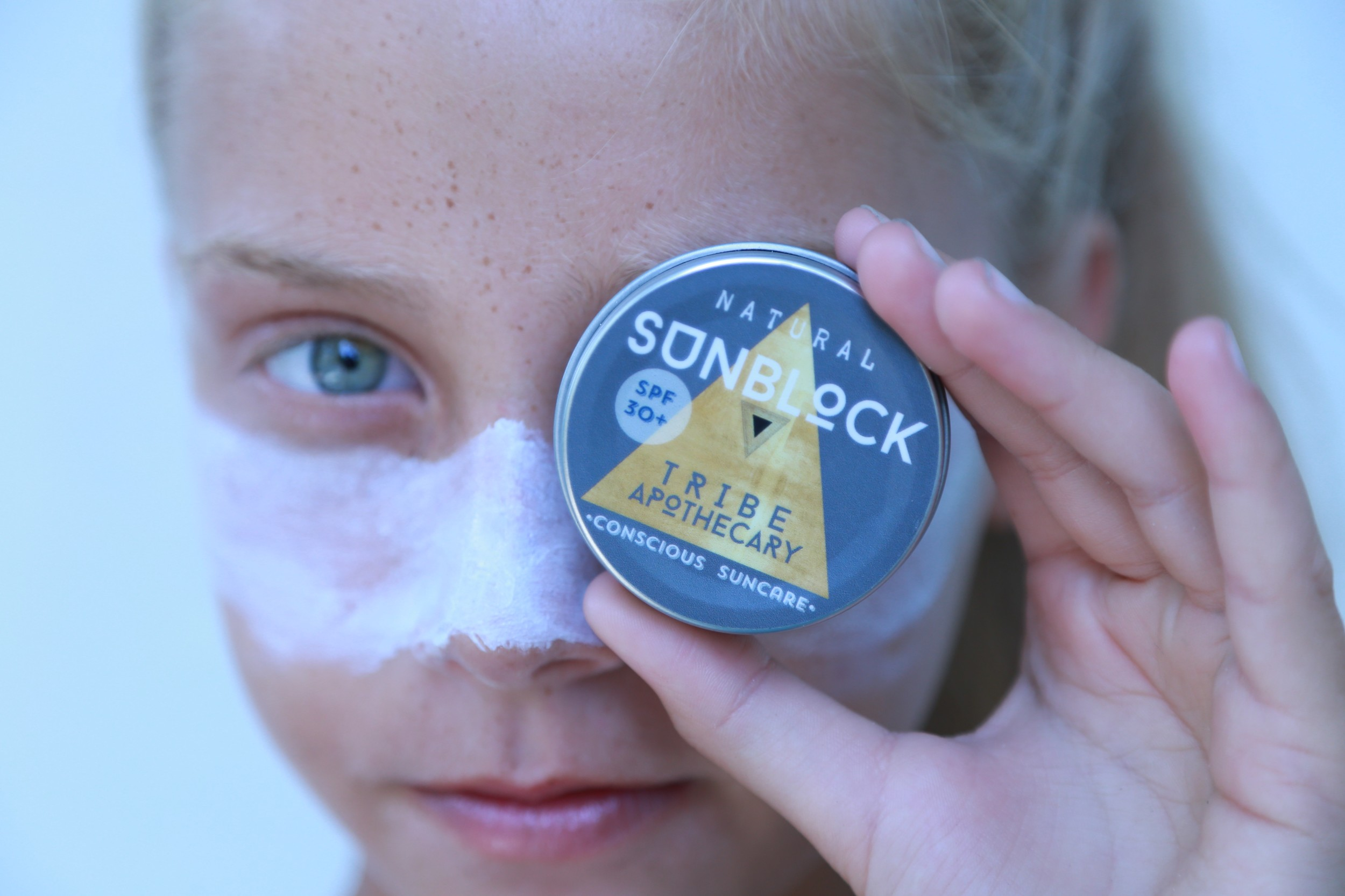 Shaylee Estes holds up a tin of the Tribe Apothecary sun block.