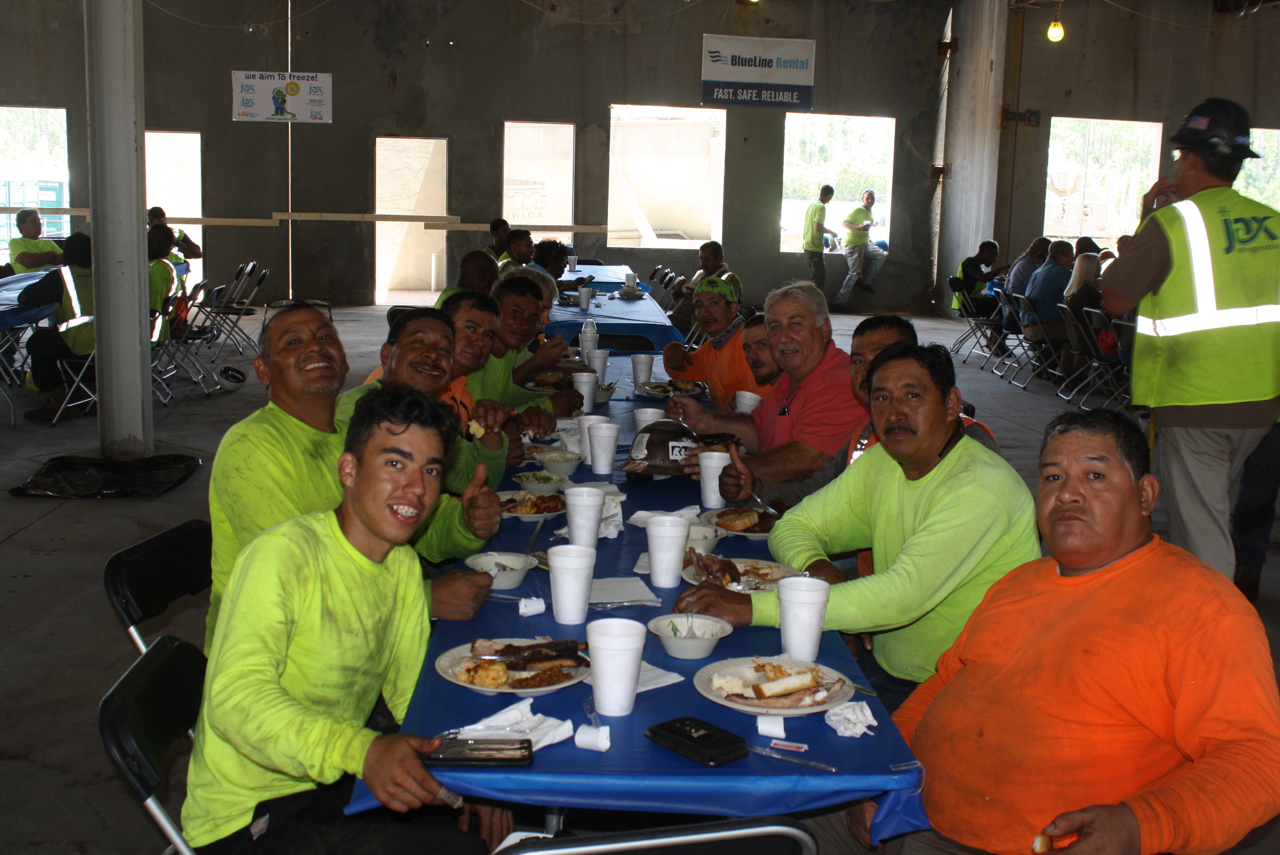 Contractors at the school construction site enjoy a barbecue lunch at the ceremony.