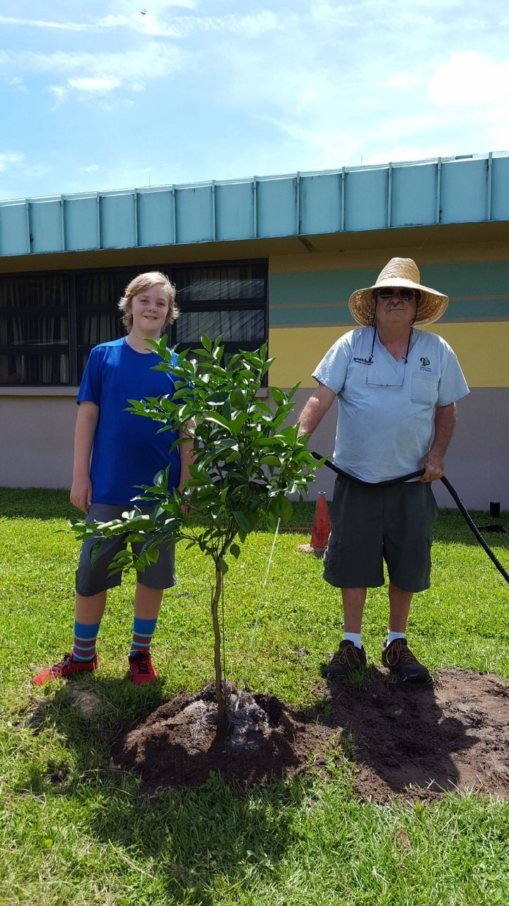 Rising sixth grade student Grayson Rigby plants the Giving Orchard's first orange tree with Mike Barwald from Flying Dragon Citrus Nursery.