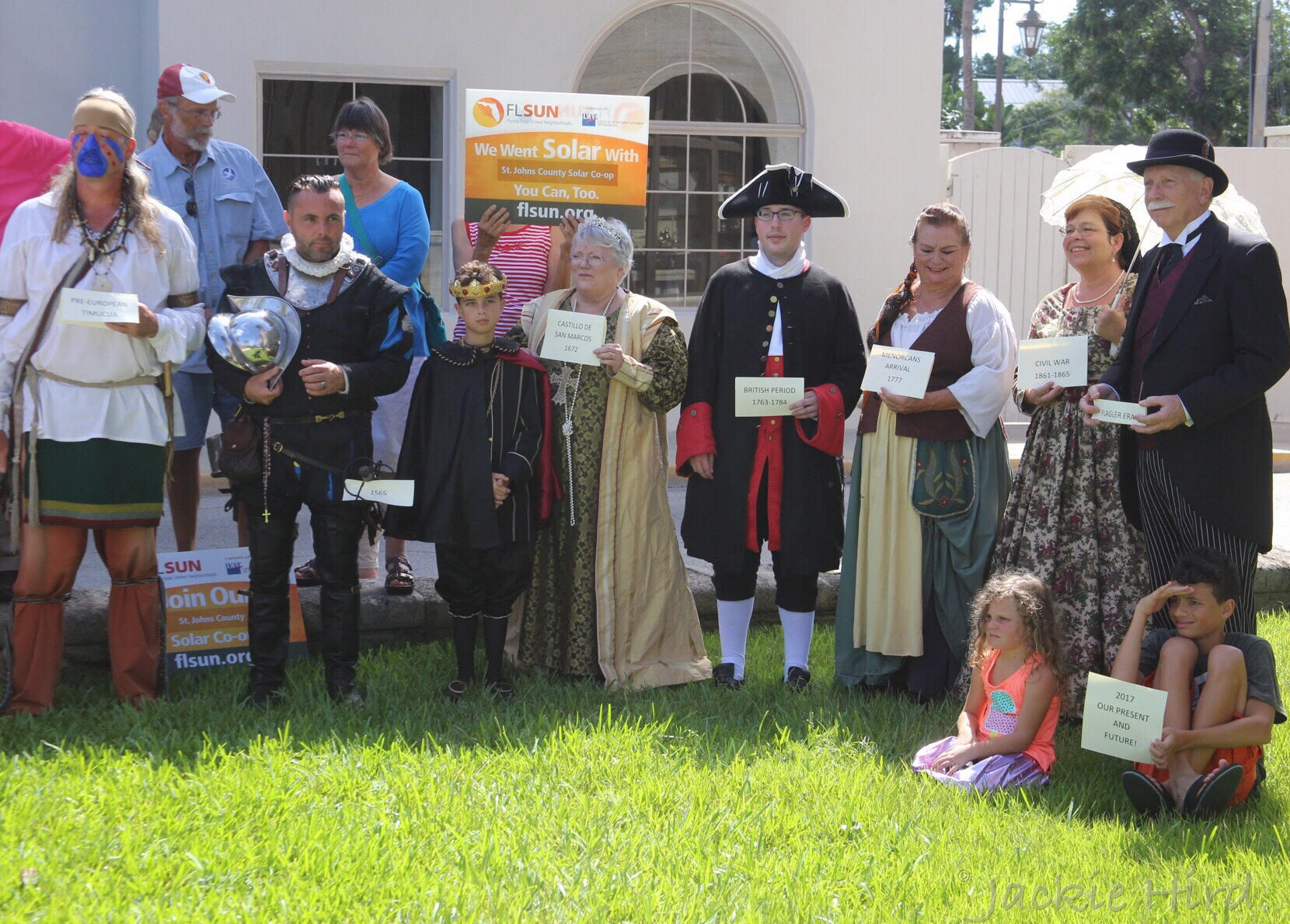 Historical re-enactors stand with signs at the solar cooperative launch event.