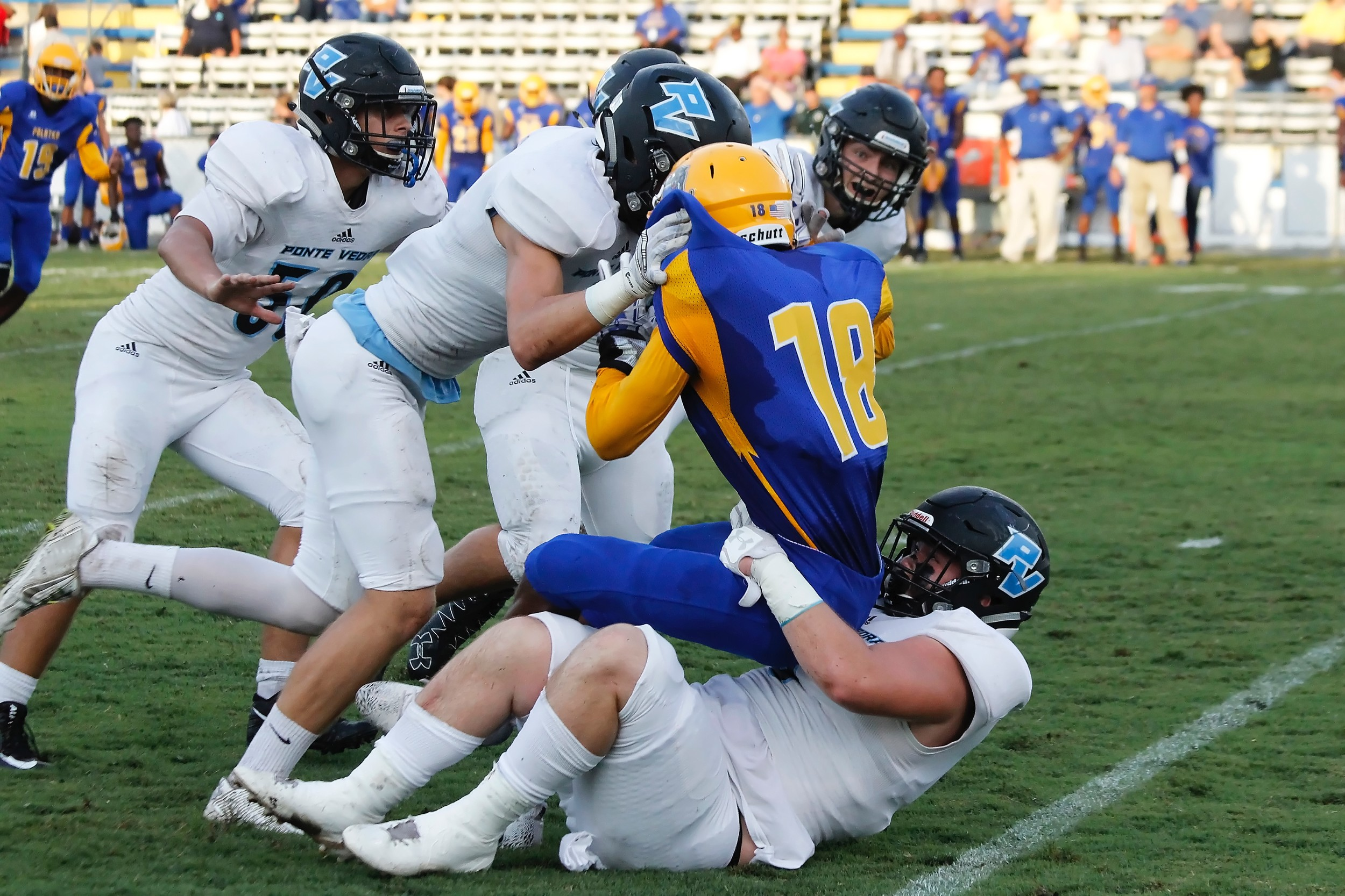 A host of Sharks with Gibson Pardue on the bottom bring down the Palatka ball carrier.