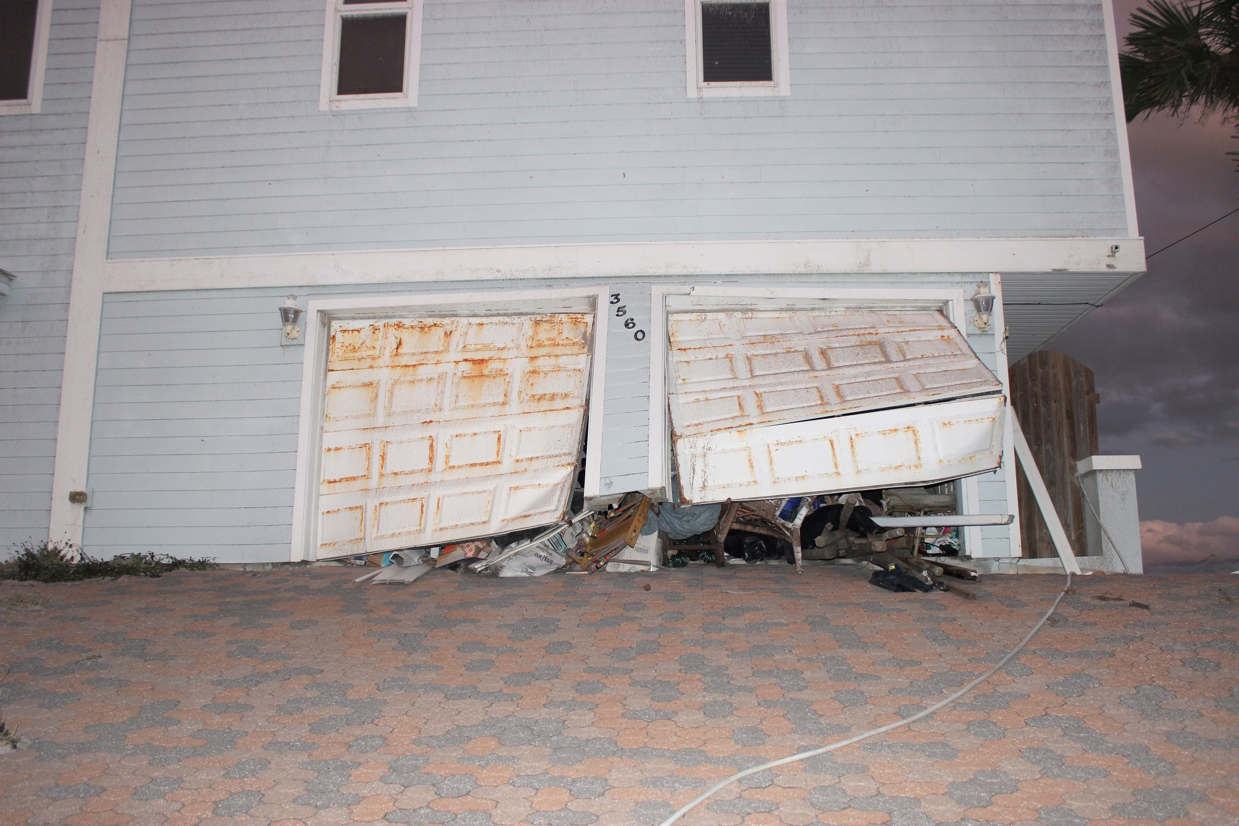 The garage doors on a Vilano Beach home are left bent and twisted after the storm.