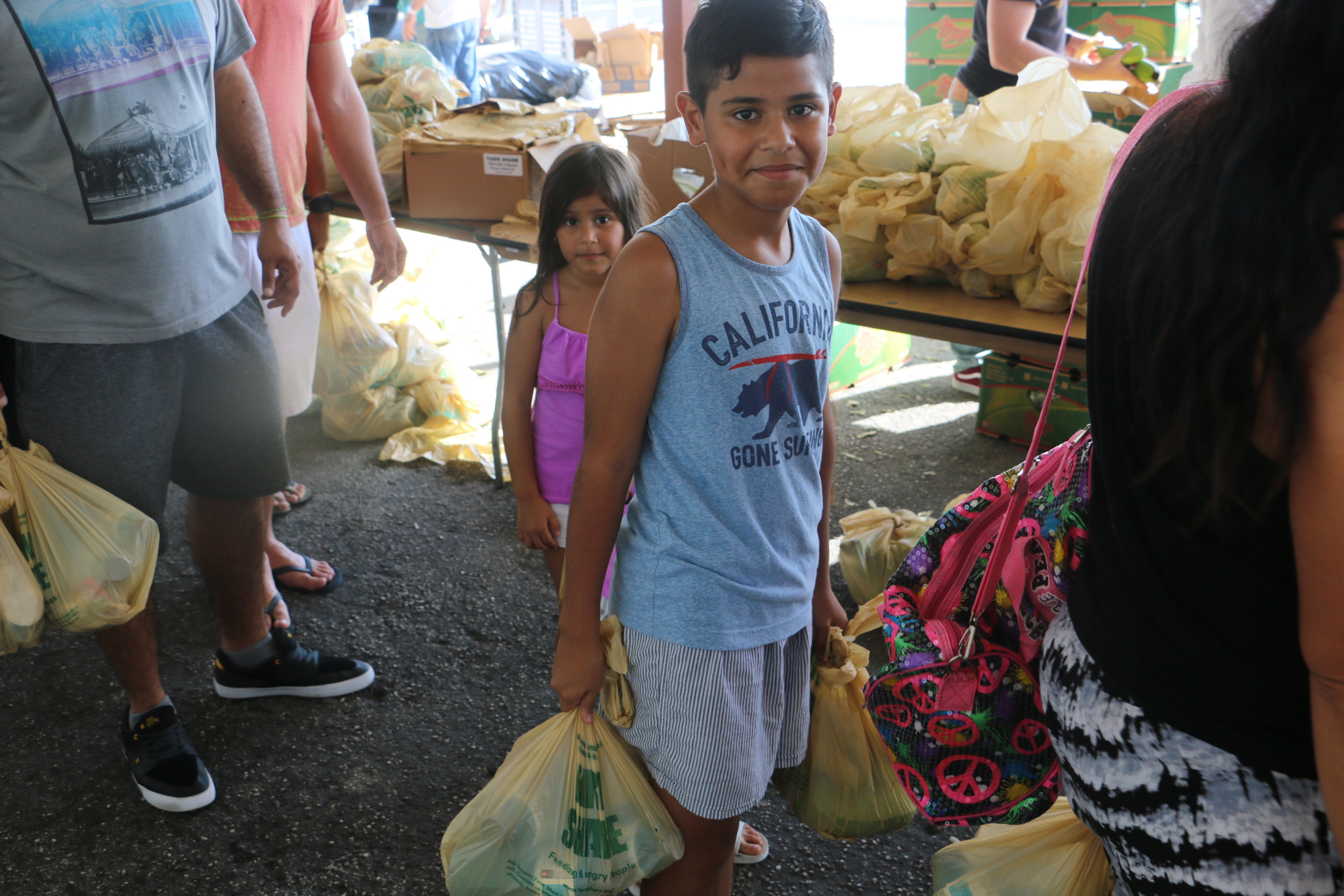 A child carries supplies provided by Farm Share to help residents in the wake of Hurricane Irma.