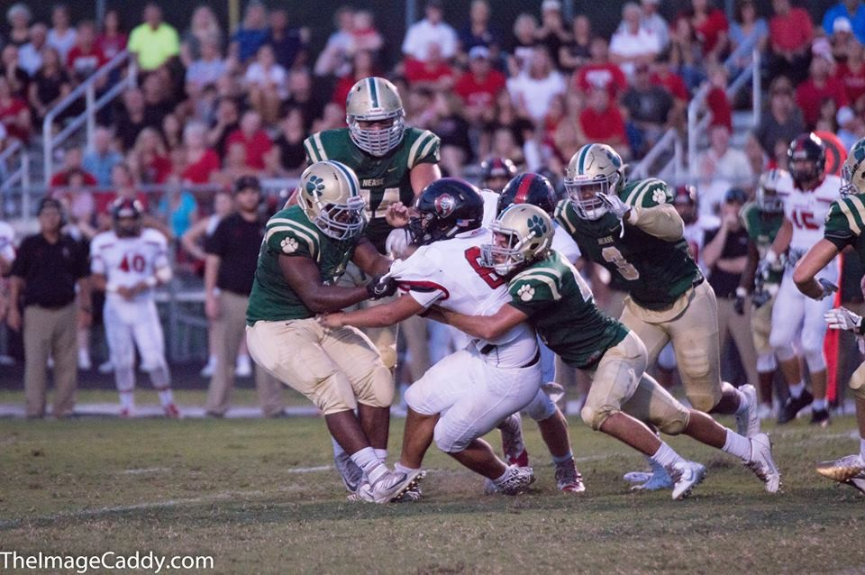 The Nease defense swarms Tai Lavatai during Friday night's homecoming game.