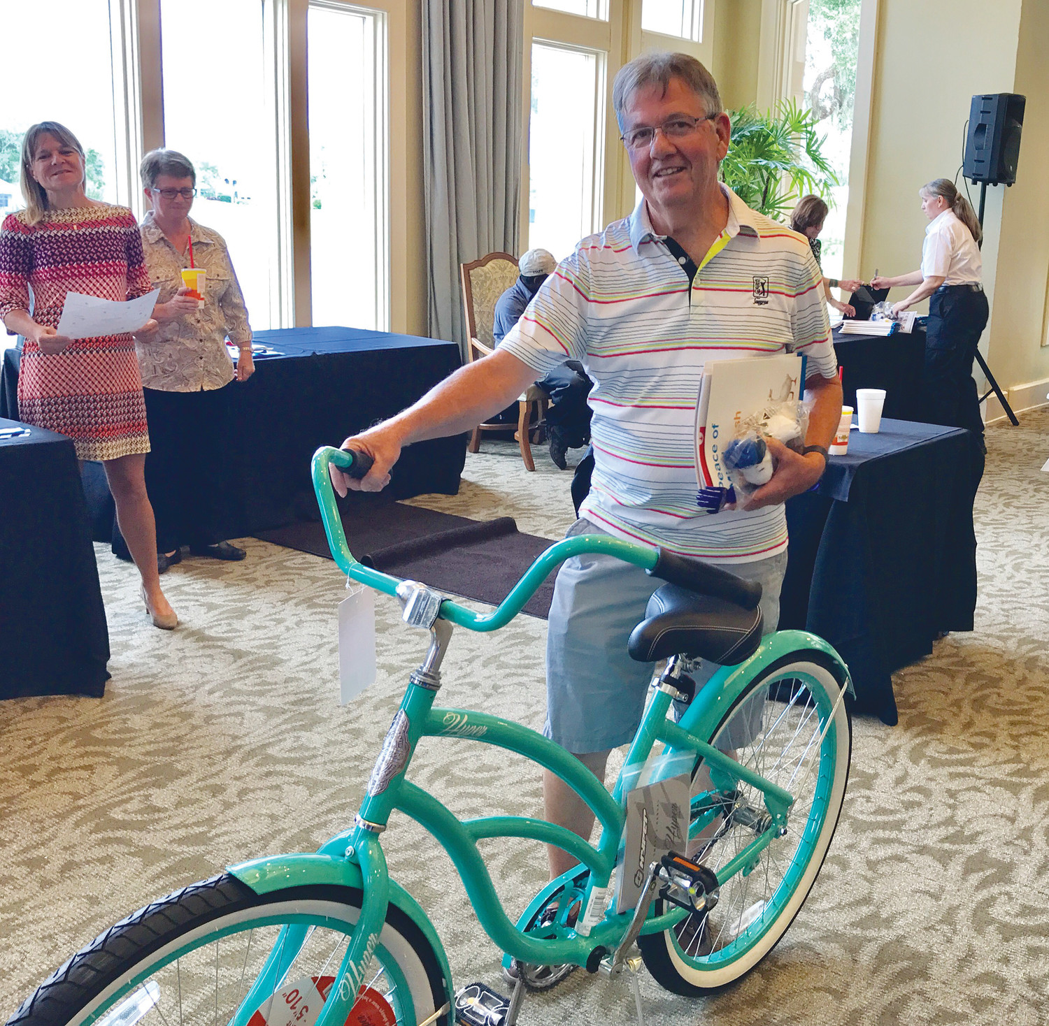 A Plantation at Ponte Vedra Beach employee wins the event's raffle prize, a beach bike donated by Hylant.