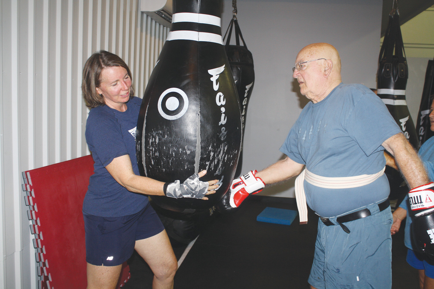 "Kristen Gray (left) guides a ""fighter"" through a boxing routine during a training session."