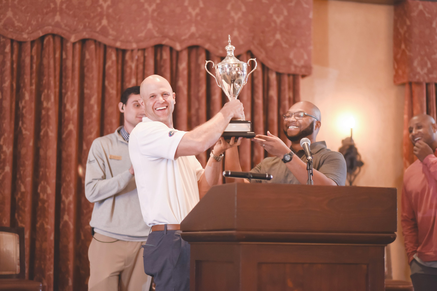 Danny Wuerffel and Demetrius Summerville, executive director of Kaley Square in Orlando (Desire Street Ministry partner), award the Desire Cup to the Florida Gators golfers, who won the tournament 32-30.