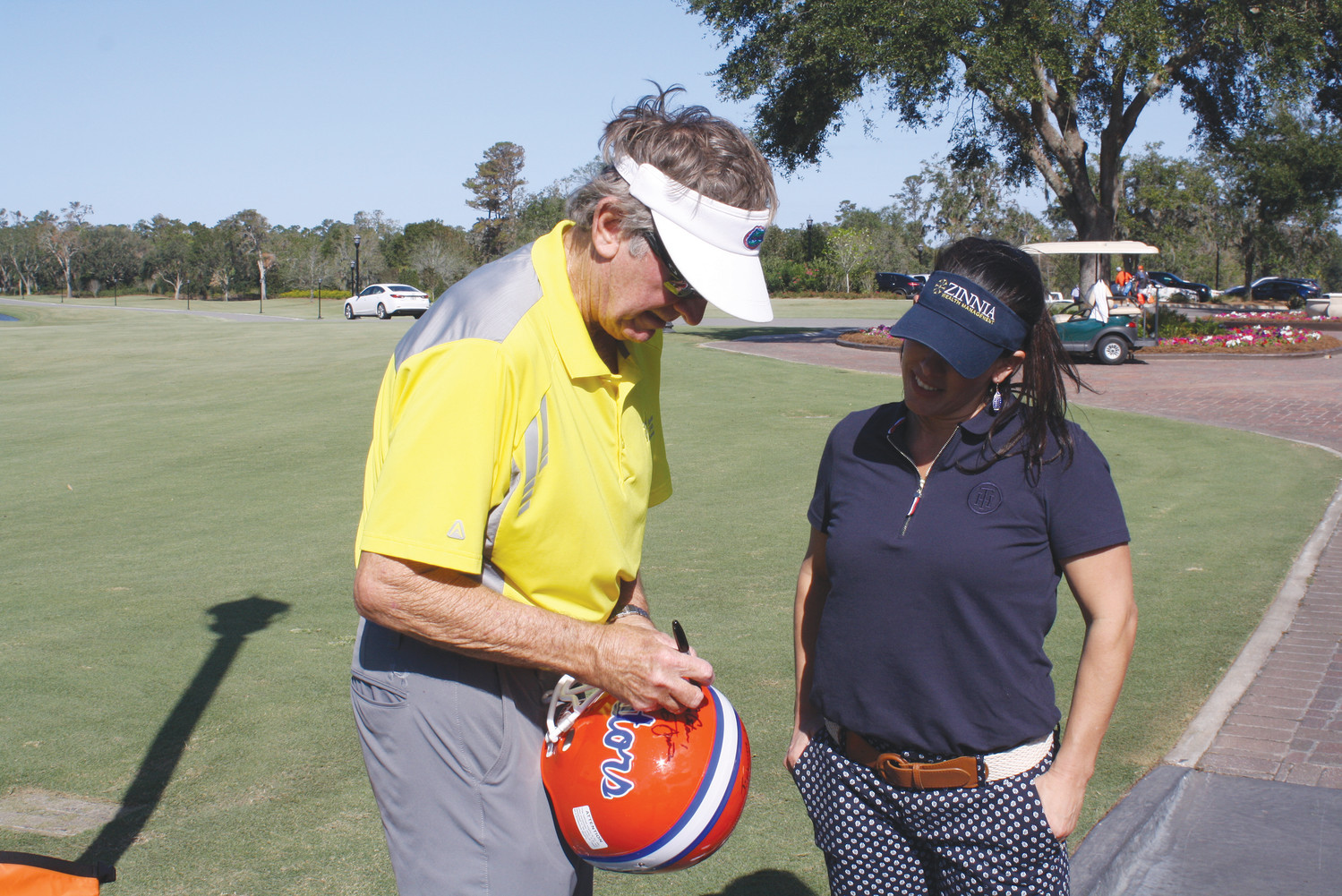 Former University of Florida football head coach Steve Spurrier signs a Gators helmet for Charisse Smith.
