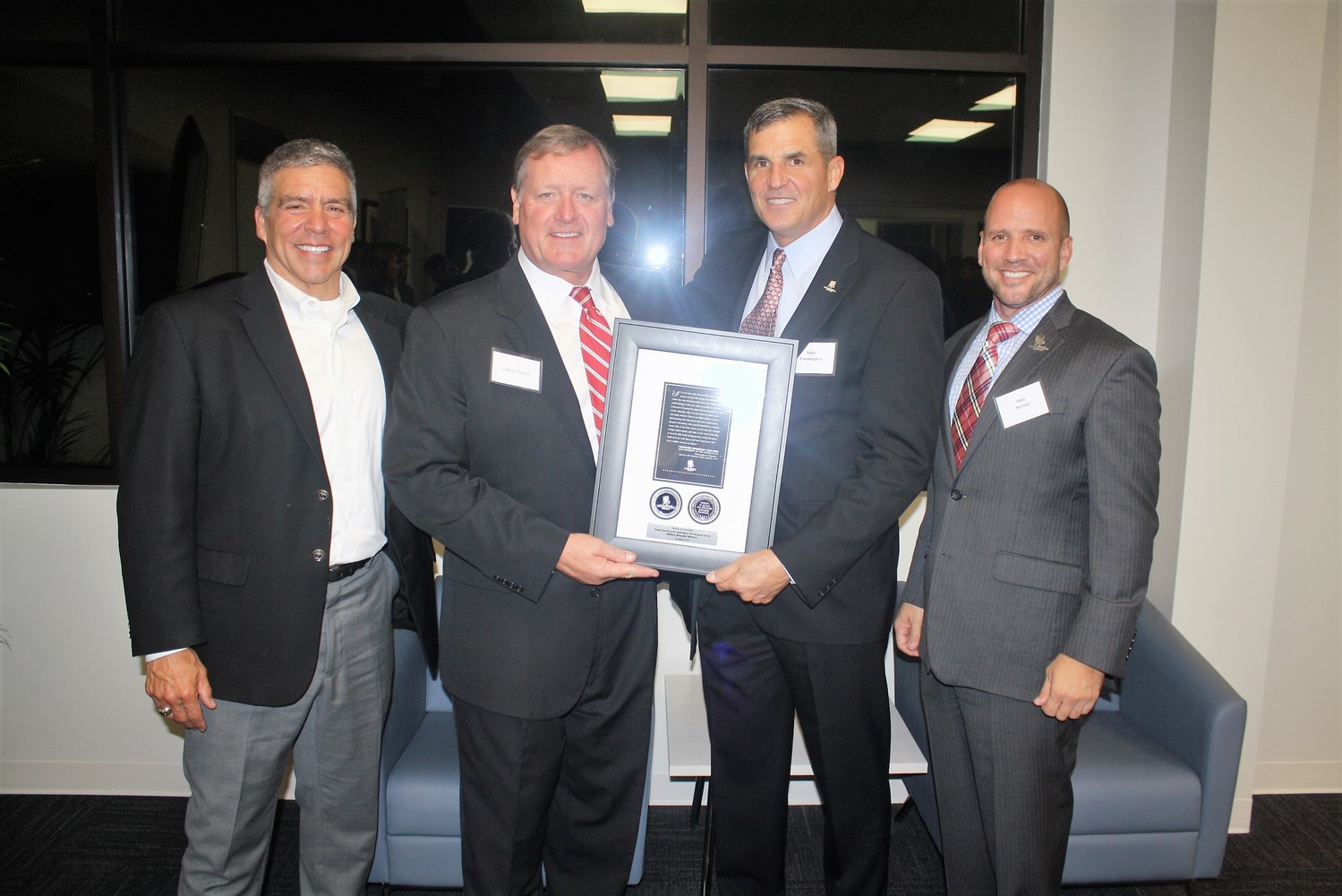 Wounded Warrior Project CEO Mike Linnington (center right) and Staff Sgt. Dan Nevins (right) present Montoya & Associates Principal Owner and Founder Will Montoya and Principal and Senior Advisor Chriss Spires with a commemorative plaque.