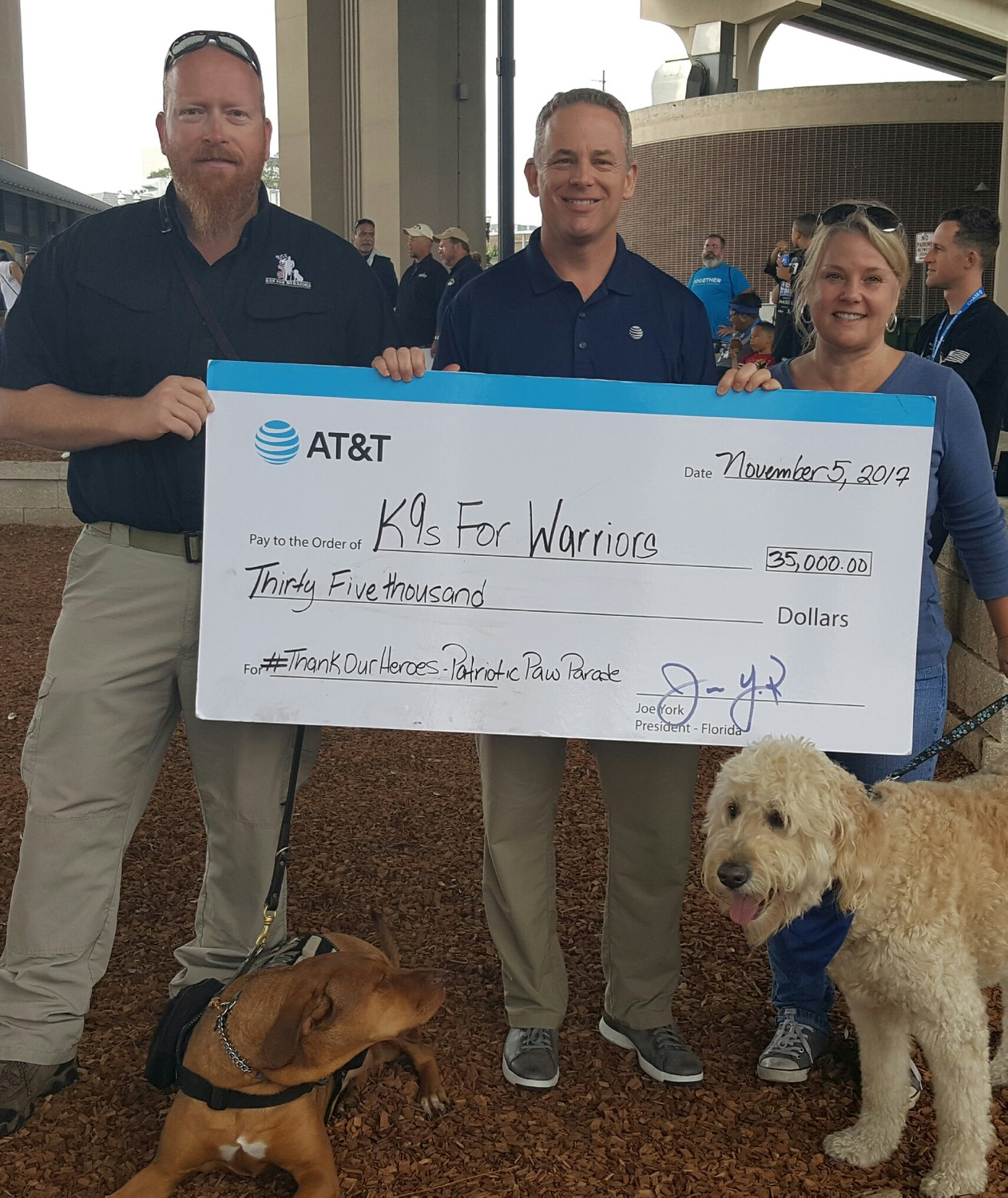 Greg Wells and Utah (left) receive a $35,000 check on behalf of K9s For Warriors from Joe York and Heather Duncan of AT&T. The company has partnered with the Ponte Vedra nonprofit as part of its Thank Our Heroes campaign. The $35,000 donation is part of a $500,000 contribution from AT&T to veterans organizations across the country.