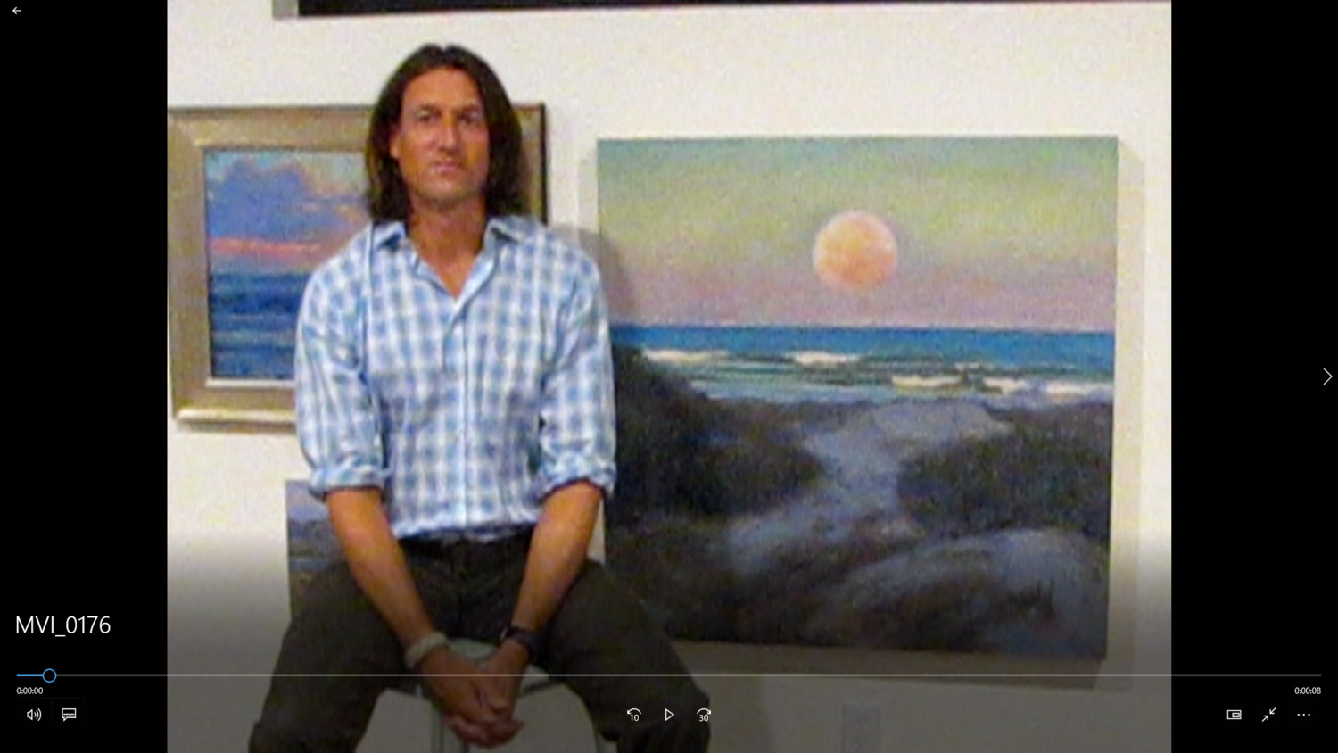 Quinn sits near his painting of the moon over the ocean at the Guana Preserve.