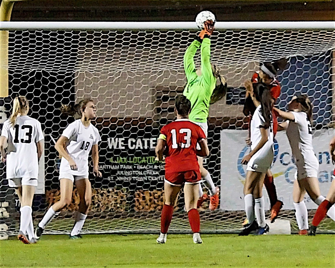 Shark goalkeeper Kaitlyn Kiel goes high to make a save on a Creekside corner kick.