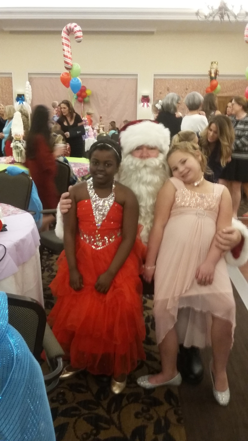 This year's guests of honor, Lunish Vurnet (left) and Cassidy Chergi, sit with Santa before the event.
