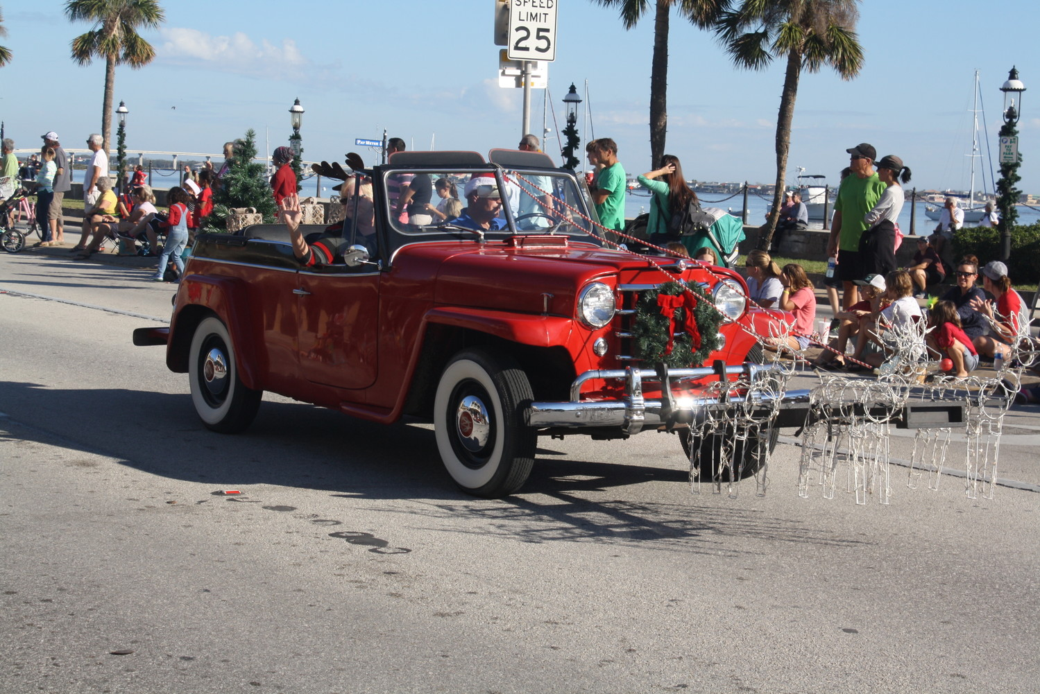 Classic cars adorned in holiday decorations stroll down the streets of the Ancient City.