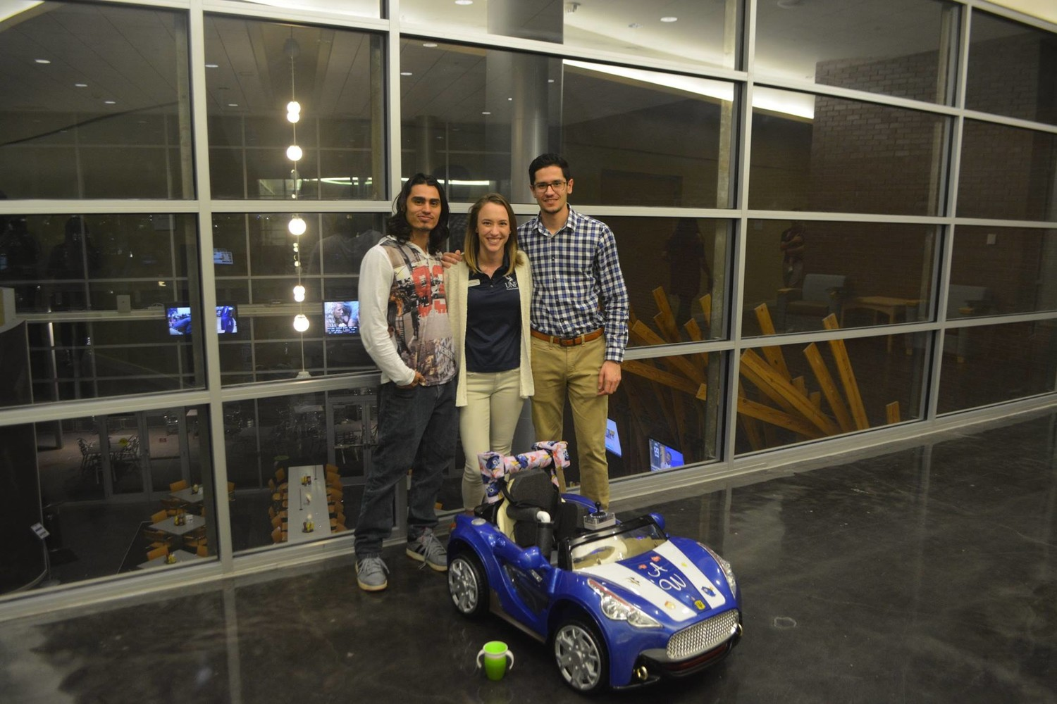 Husam Safar (right) poses for a picture with his teammates, behind their toy car creation.