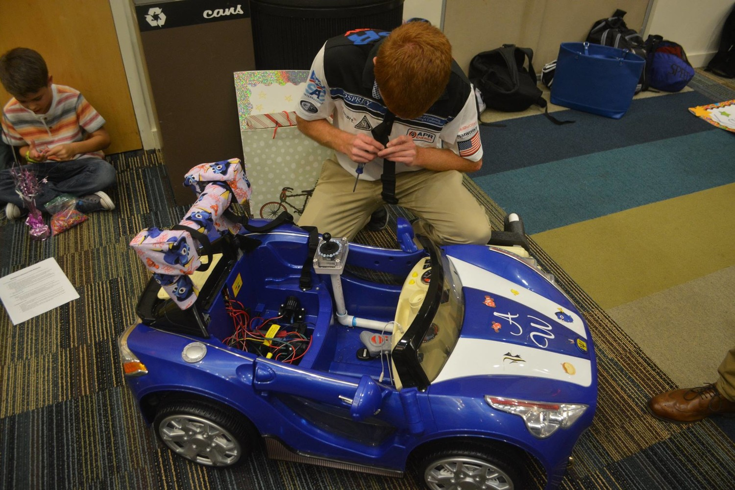 A UNF student does some last-minute adjustments to a toy car.