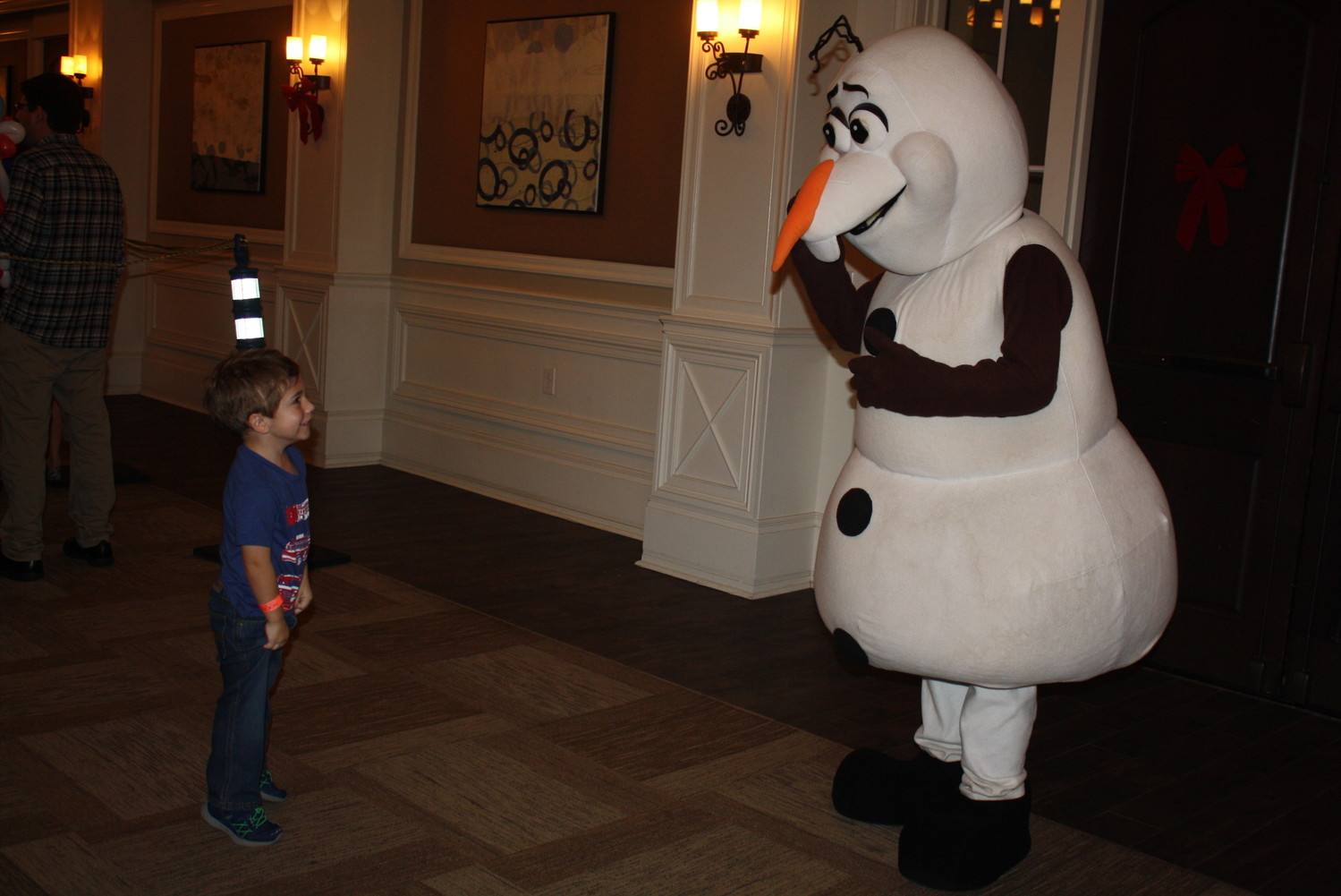 "A boy enjoys a meet-and-greet with Olaf from ""Frozen."""