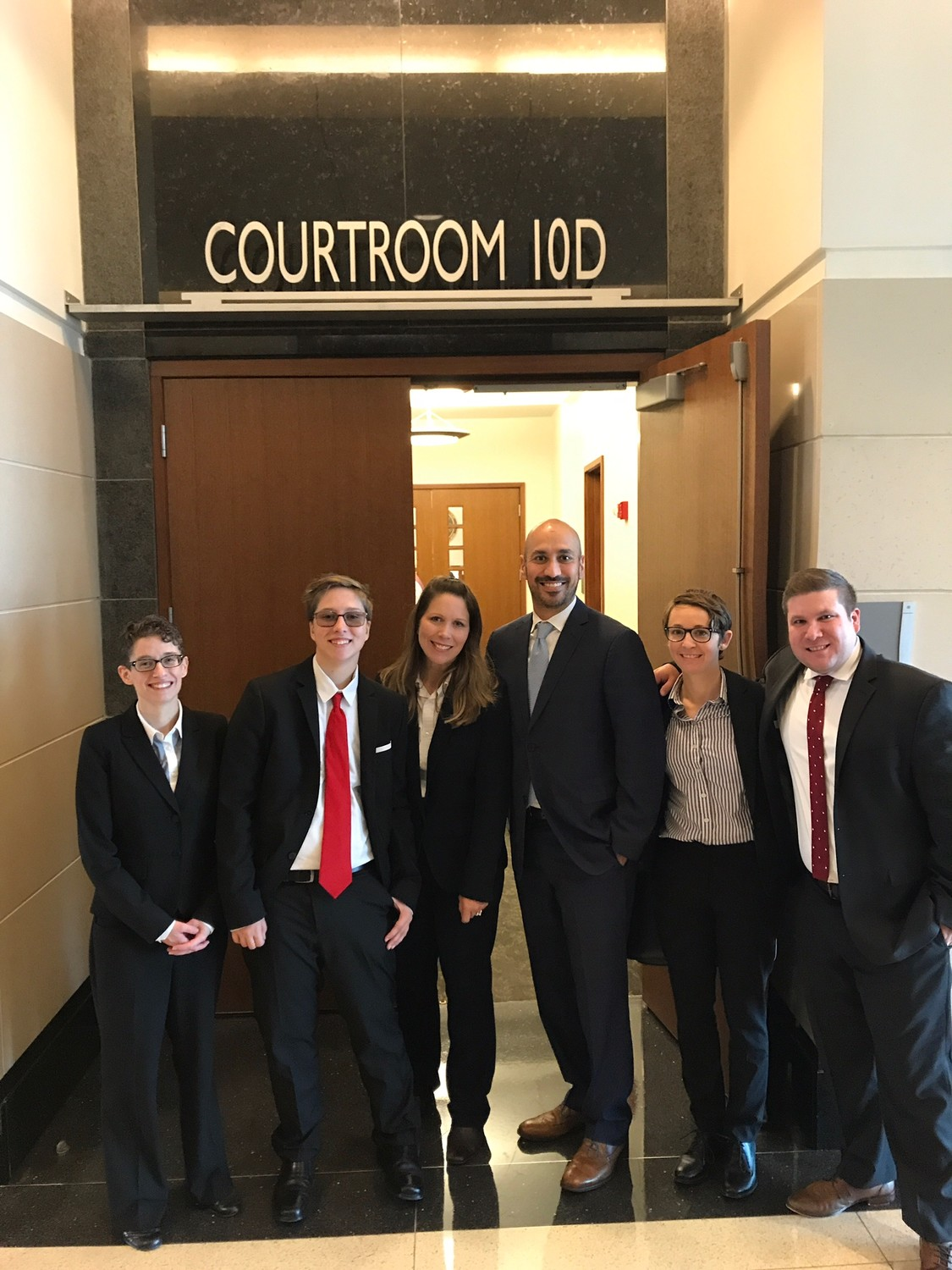Drew Adams (second from left) and his mother Erica Kasper (third from left) gather with the Lambda Legal attorneys during last week's federal trial in Jacksonville.