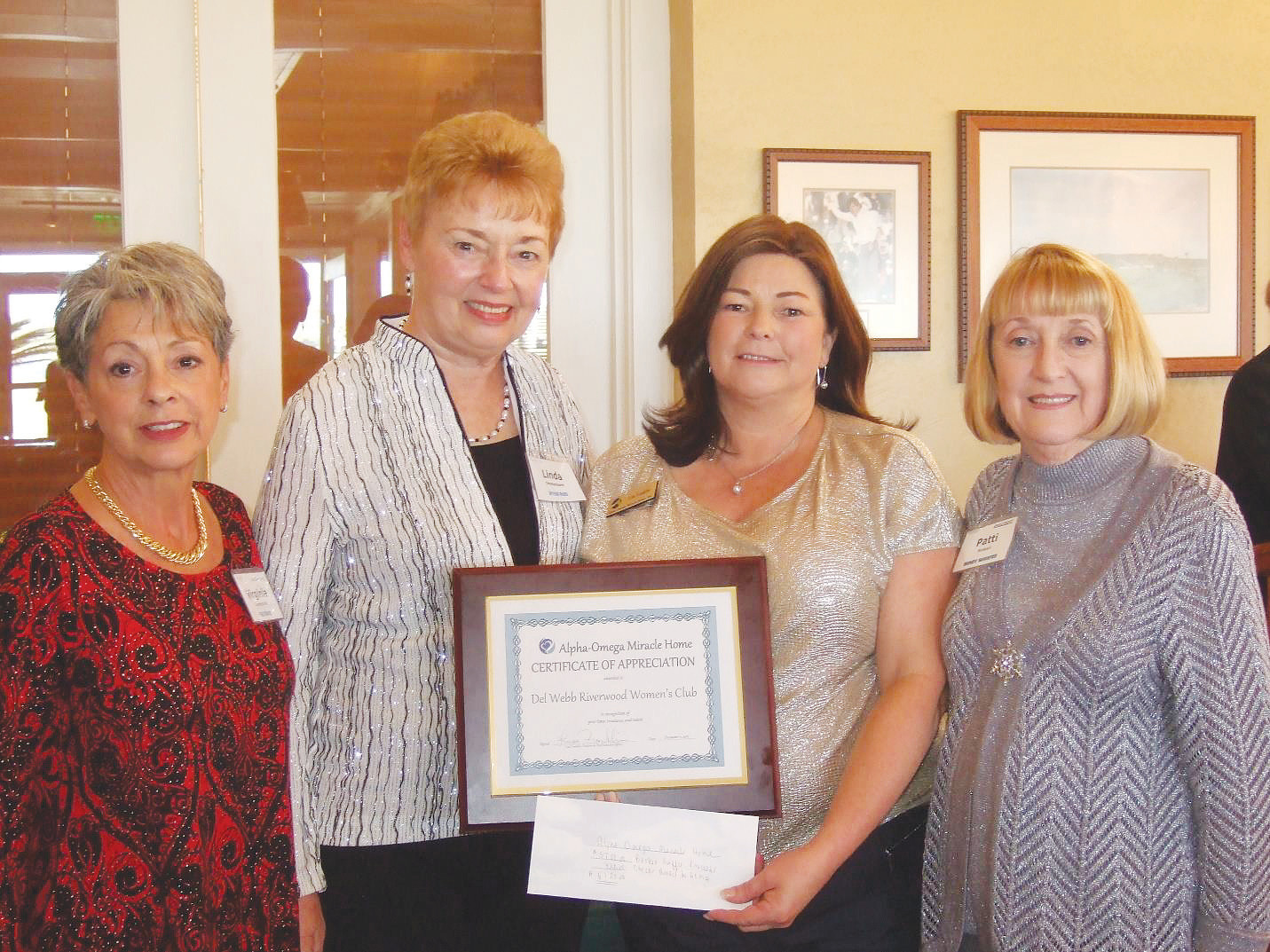 Riverwood Women's Club presents a check to Alpha-Omega Miracle Home and receives a Certificate of Appreciation. Left to right: Virginia Marchesiello and Linda Ommerborn, co-chairs of the Women's Club Outreach Committee; Lisa Franklin, founder and CEO of The Alpha-Omega Miracle Home; and Patti Russell, president of the Riverwood Women's Club.