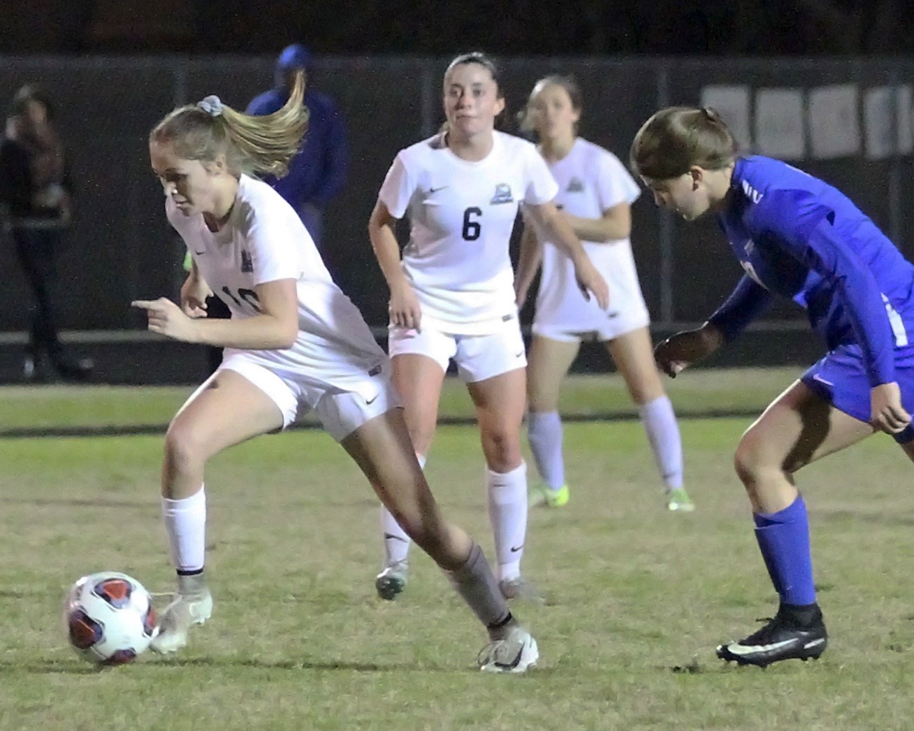The Sharks' Kai Hayes races past the Pedro defender as Molly Miller looks on.