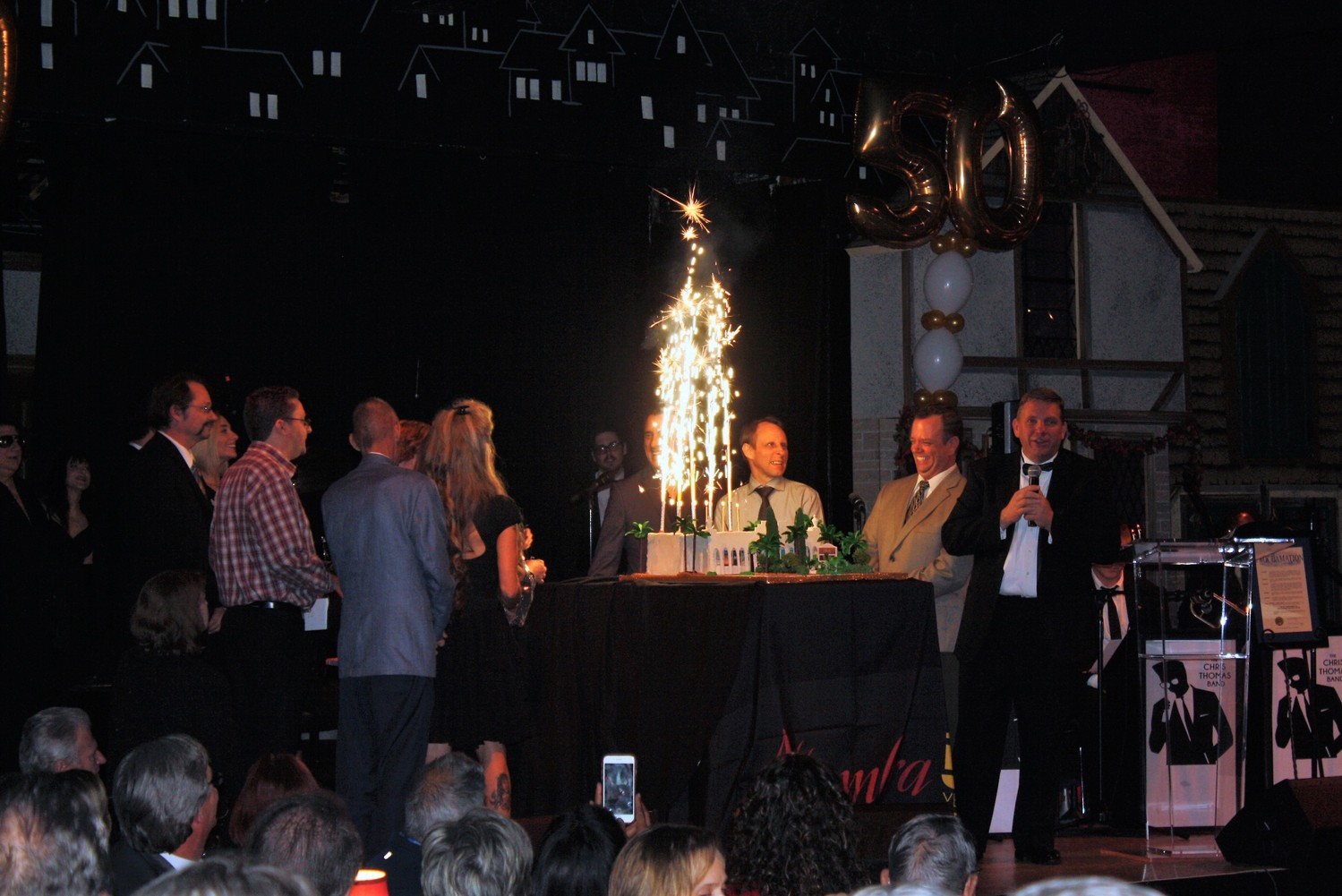 Alhambra staff gathers on stage to light the birthday cake's sparkler candles.