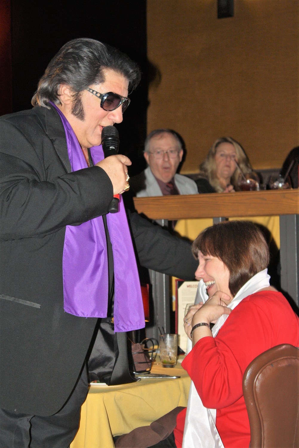 Elvis Presley (portrayed by Rick Marino) works the crowd, bestowing an audience member with a scarf.