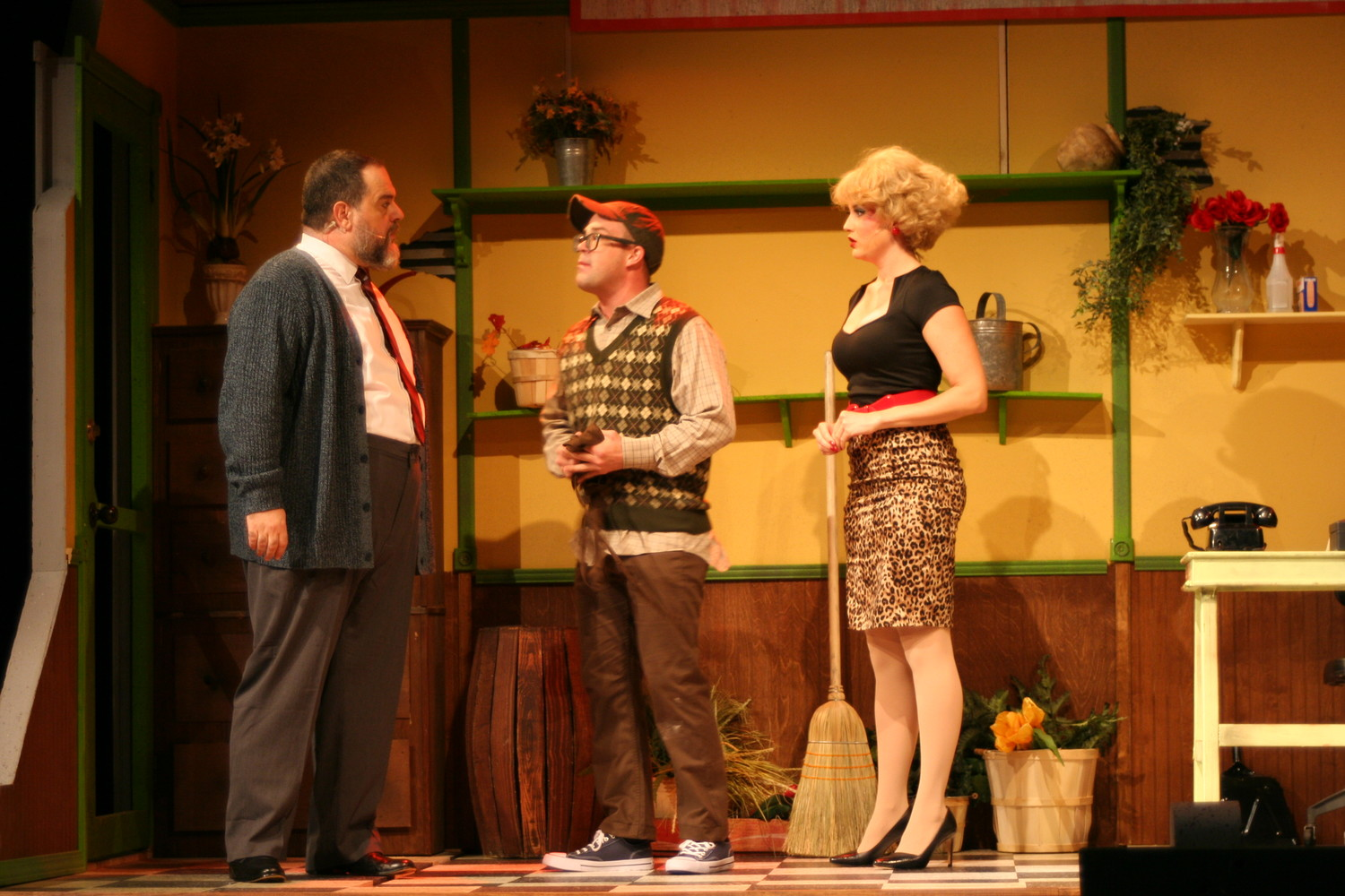 Seymour (center) and Audrey converse with their boss, Mr. Mushnik, at the flower shop