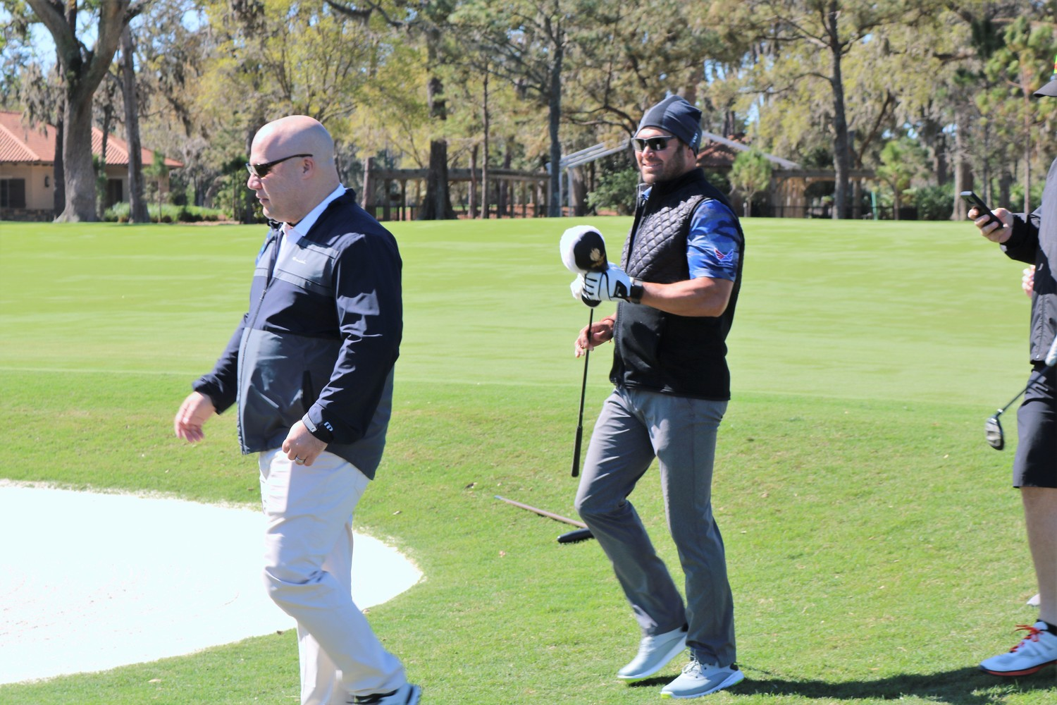 Retired Major League Baseball player Johnny Damon (center) makes his way back to his golf cart.