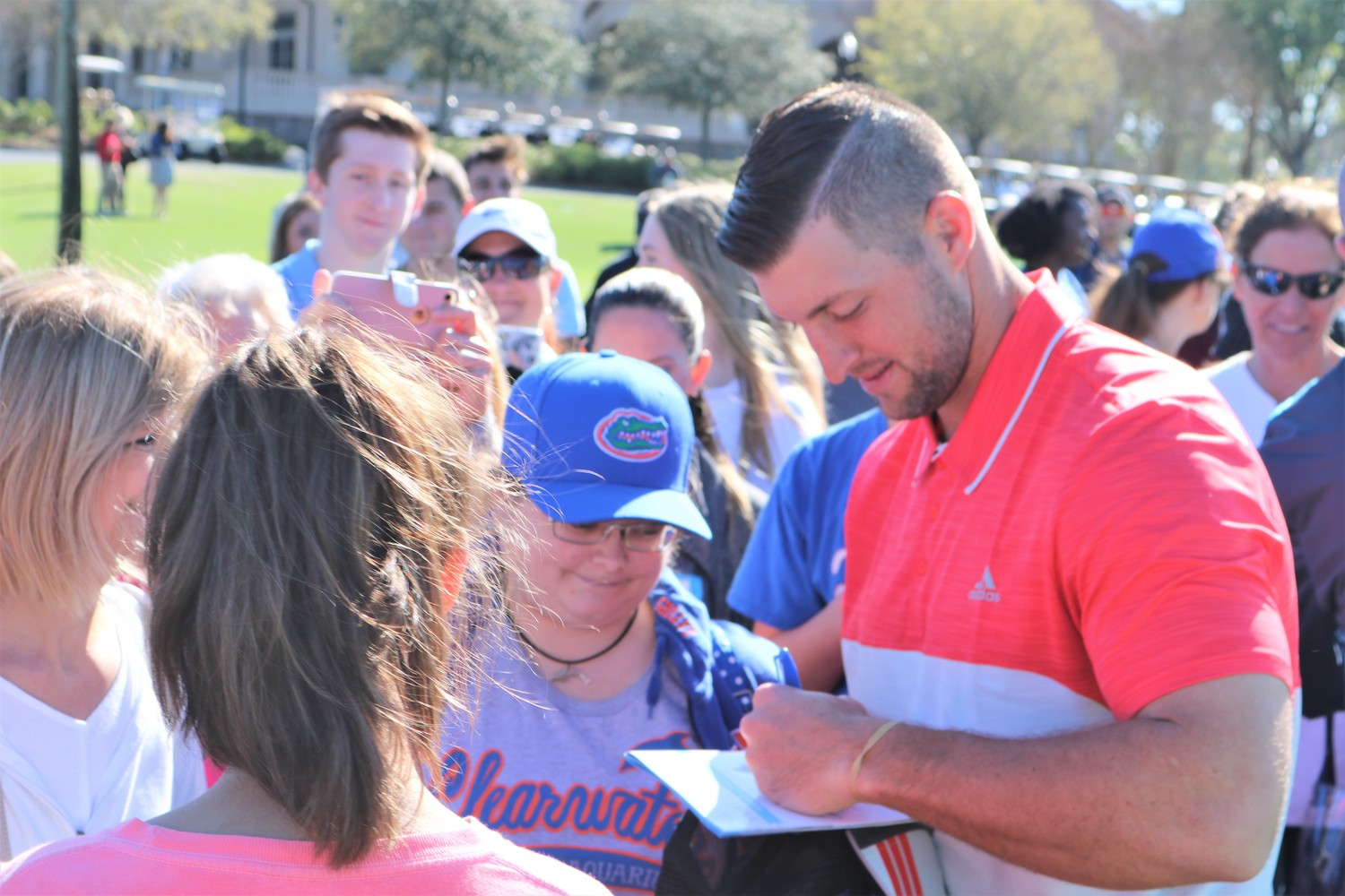 Tim Tebow signs autographs before the start of the tournament.