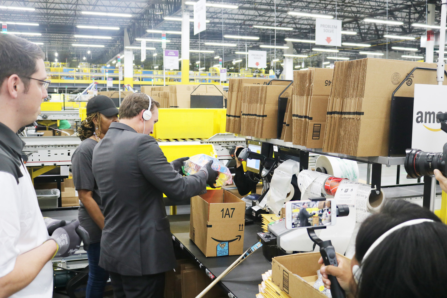 Mayor Curry packs and readies a box for shipment at Amazon's Pecan Park Road fulfillment center in Jacksonville.