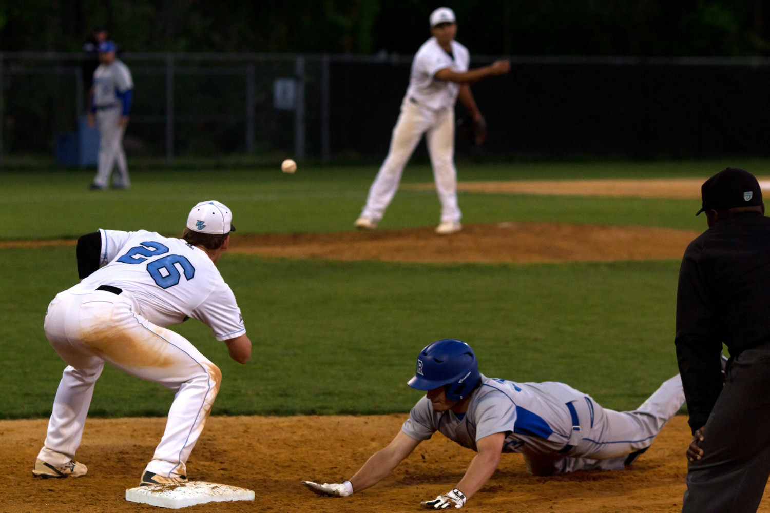 The Ridgeview runner dives back to first safely as Sharks' first baseman Tony Roca awaits the throw.