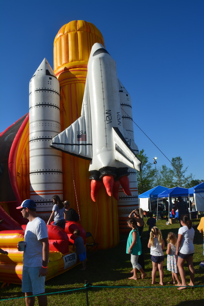Kids line up to play on an inflatable slide at the Roscolusa Songwriters Festival.
