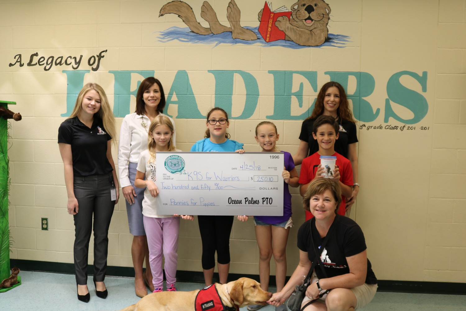 OPES students and staff present a check for $250.10 to K9s for Warriors after holding a fundraiser at a recent book fair.