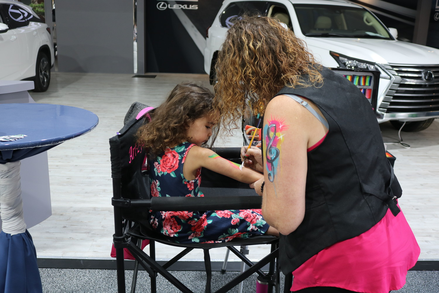 A child gets her arm painted with an artistic design at the Community PedsCare event.