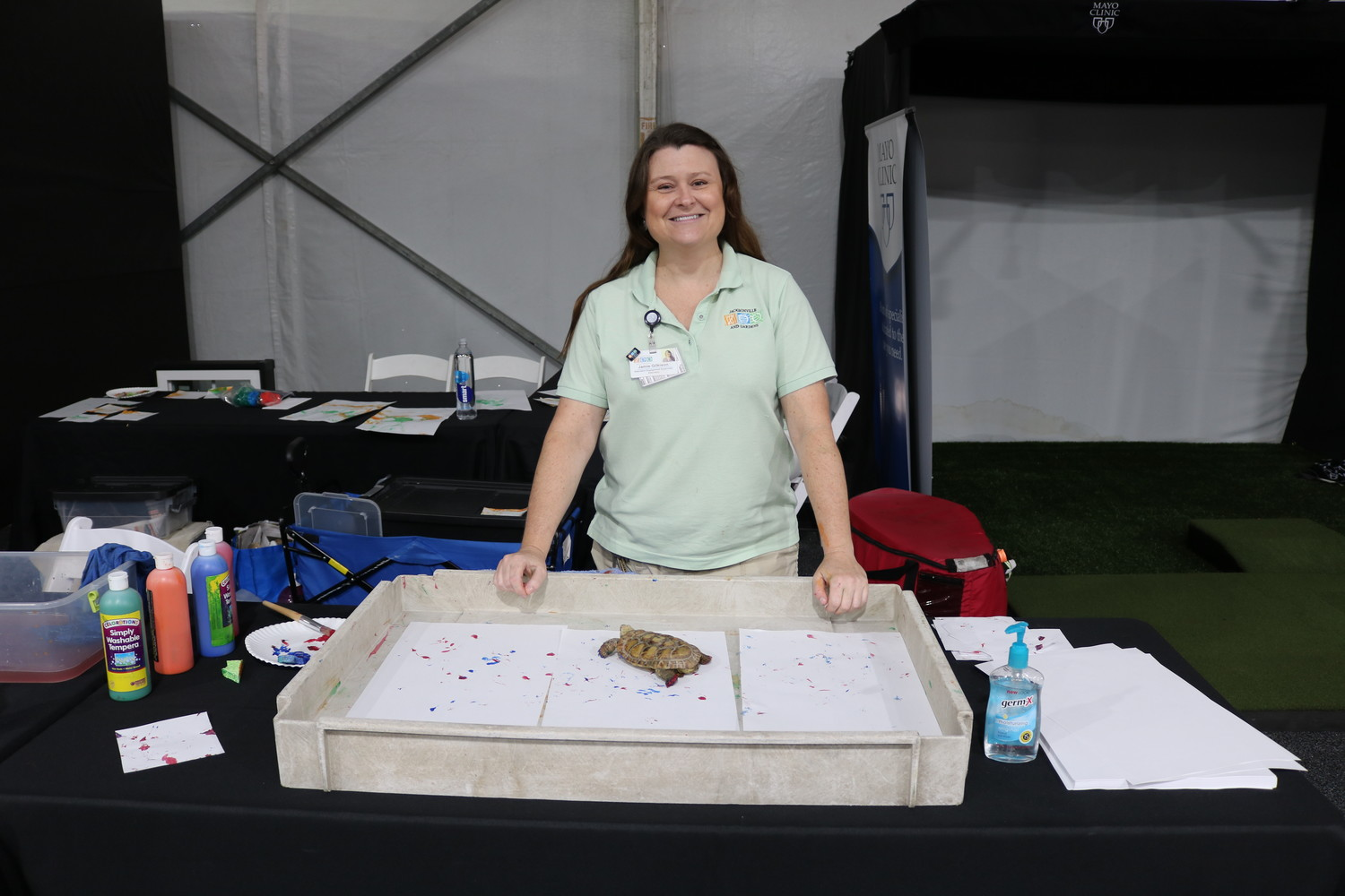 Jamie Gilkison, an education engagement supervisor with the Jacksonville Zoo, poses for a photo behind the Jacksonville Zoo's booth.