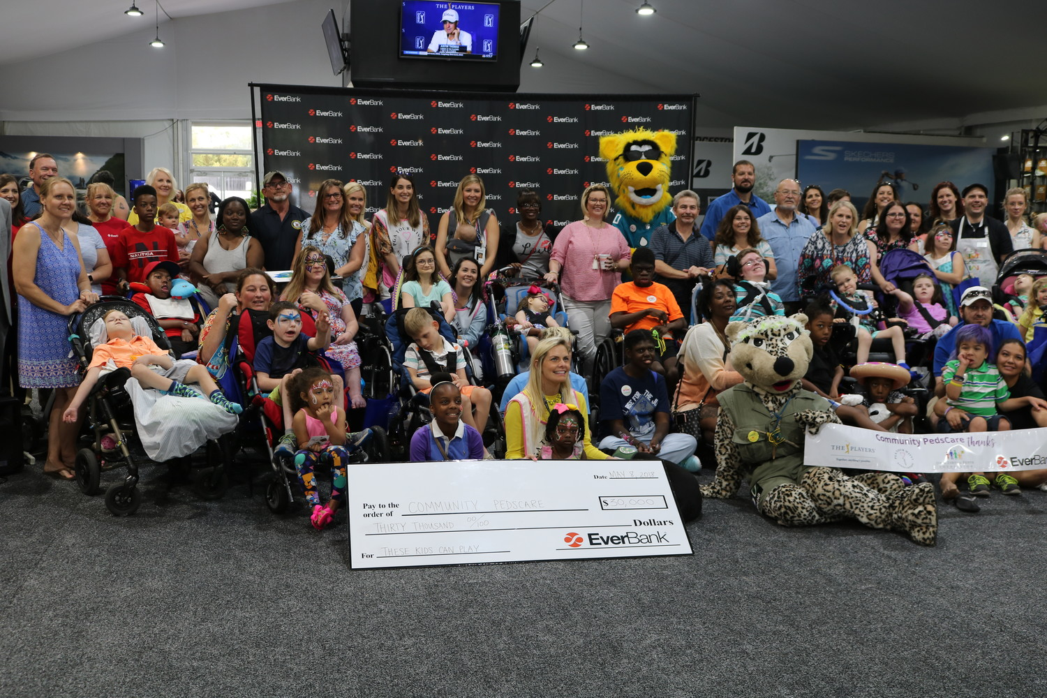 "Attendees of the ""These Kids Can Paint"" event held May 8 at THE PLAYERS Championship pose for a photo with a $30,000 check for Community PedsCare courtesy of EverBank."
