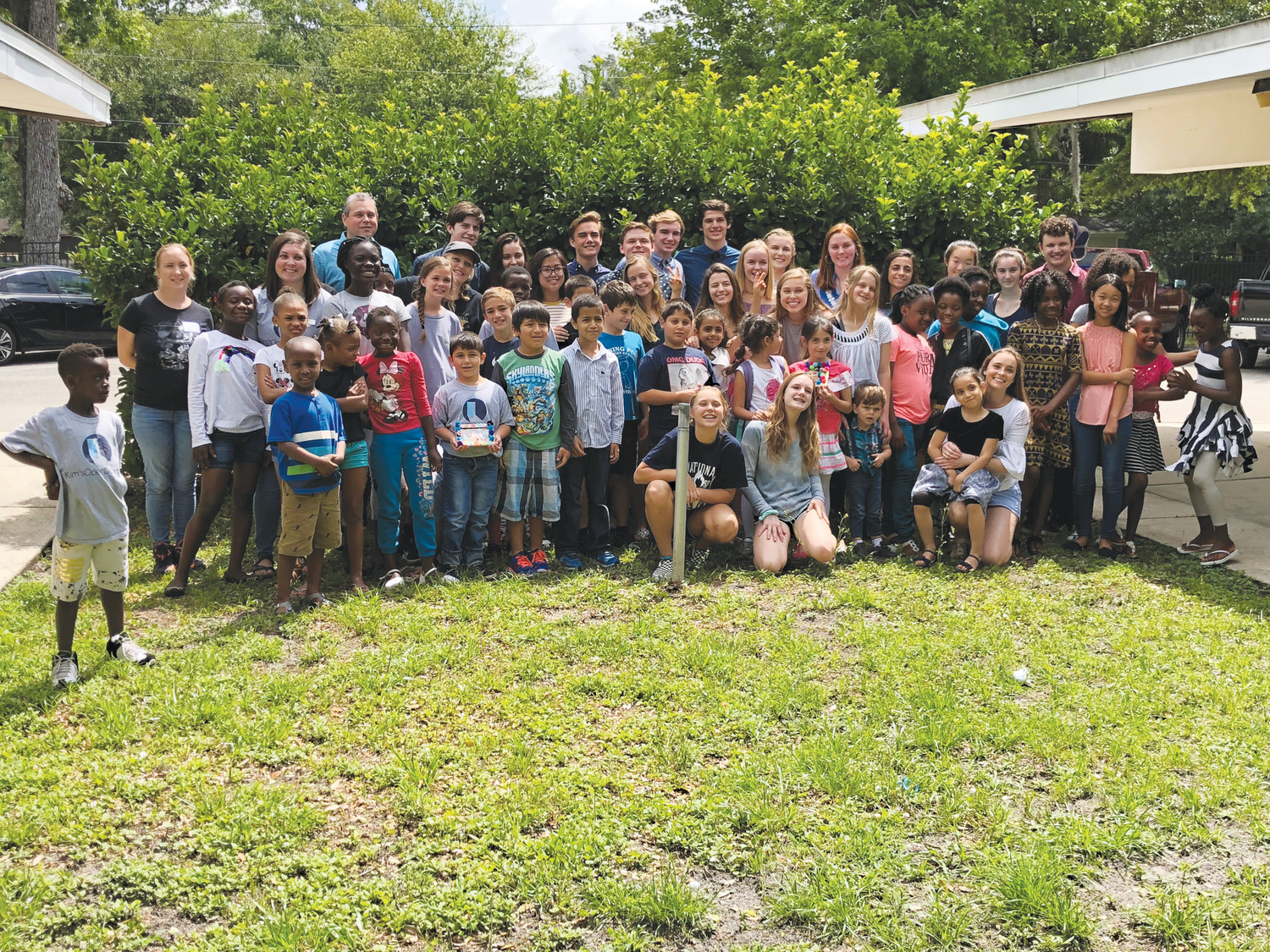 Refugee children pose with JaxTHRIVE volunteers at the nonprofit's first graduation celebration May 19.