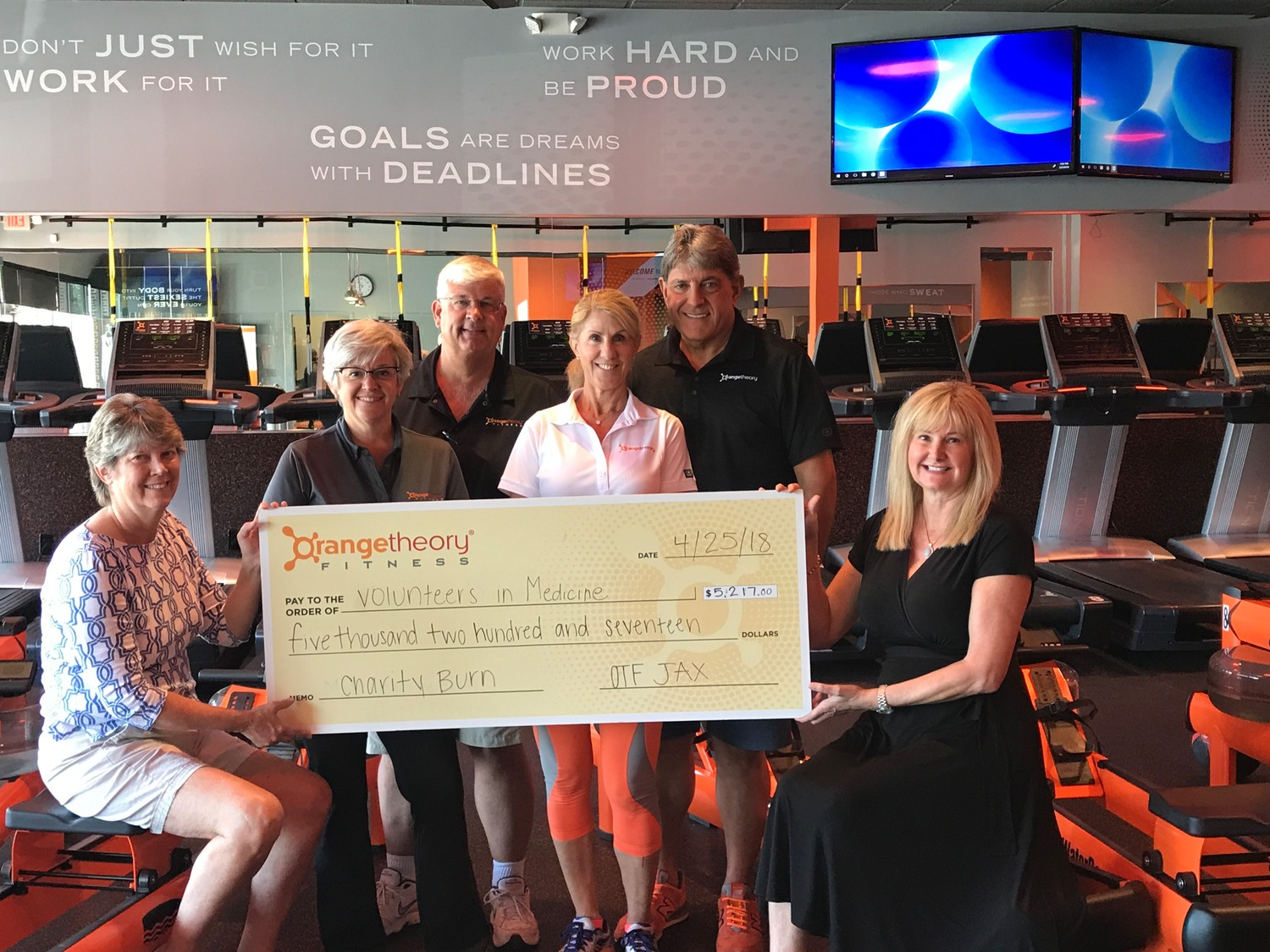 Volunteers in Medicine CEO Mary Pat Corrigan (far left) and 2018 April Woman With Heart Leslie Gordon (far right) are presented with a donation from Orangetheory Fitness owners (from center left) Donna and Rick Fenchel and Leslie and George Baccash.