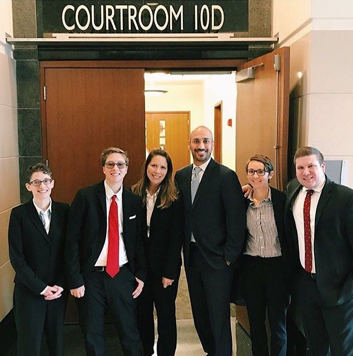 Drew Adams (second from left) and his mother Erica Kasper (third from left) gather with the Lambda Legal attorneys following a federal trial in Jacksonville.