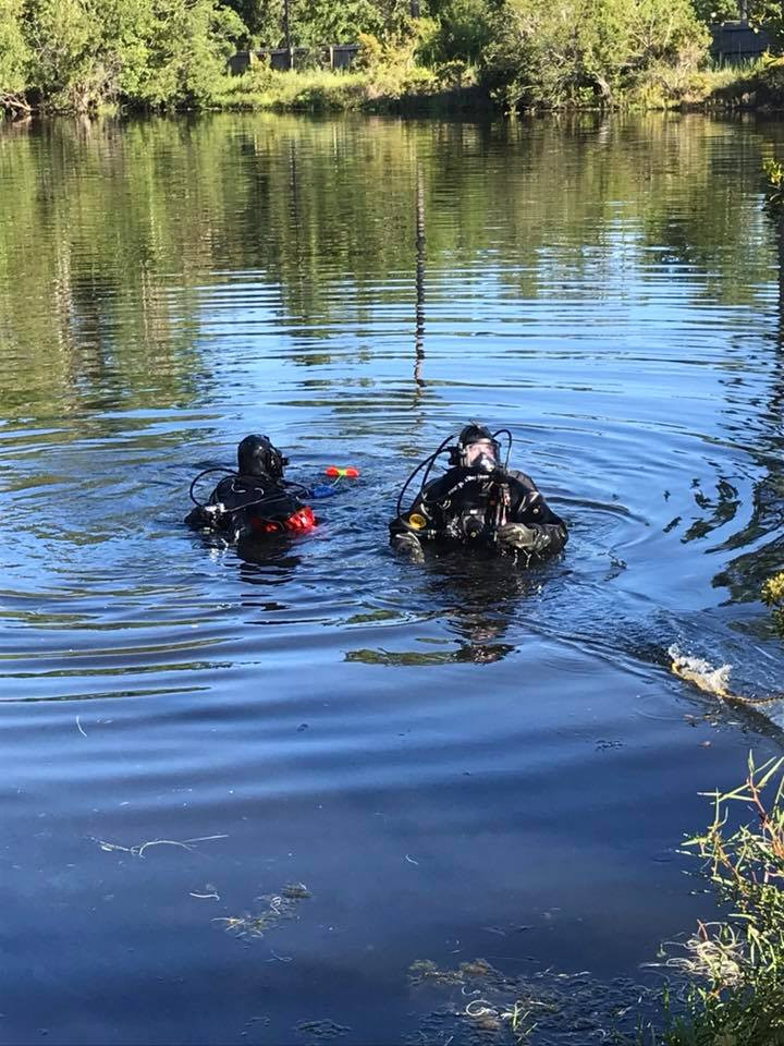 Divers work to retrieve a yellow motorcycle from a retention pond.