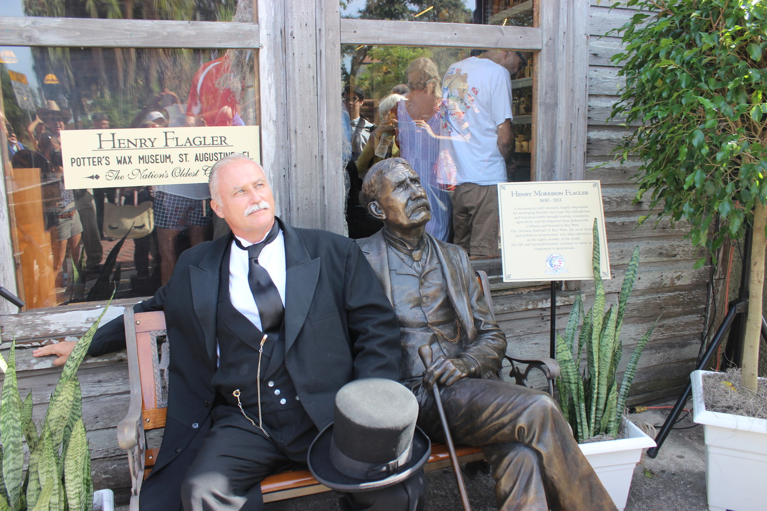 John Stavely sits next to the new Henry Flagler bronze sculpture outside Potter's Wax Museum in downtown St. Augustine.