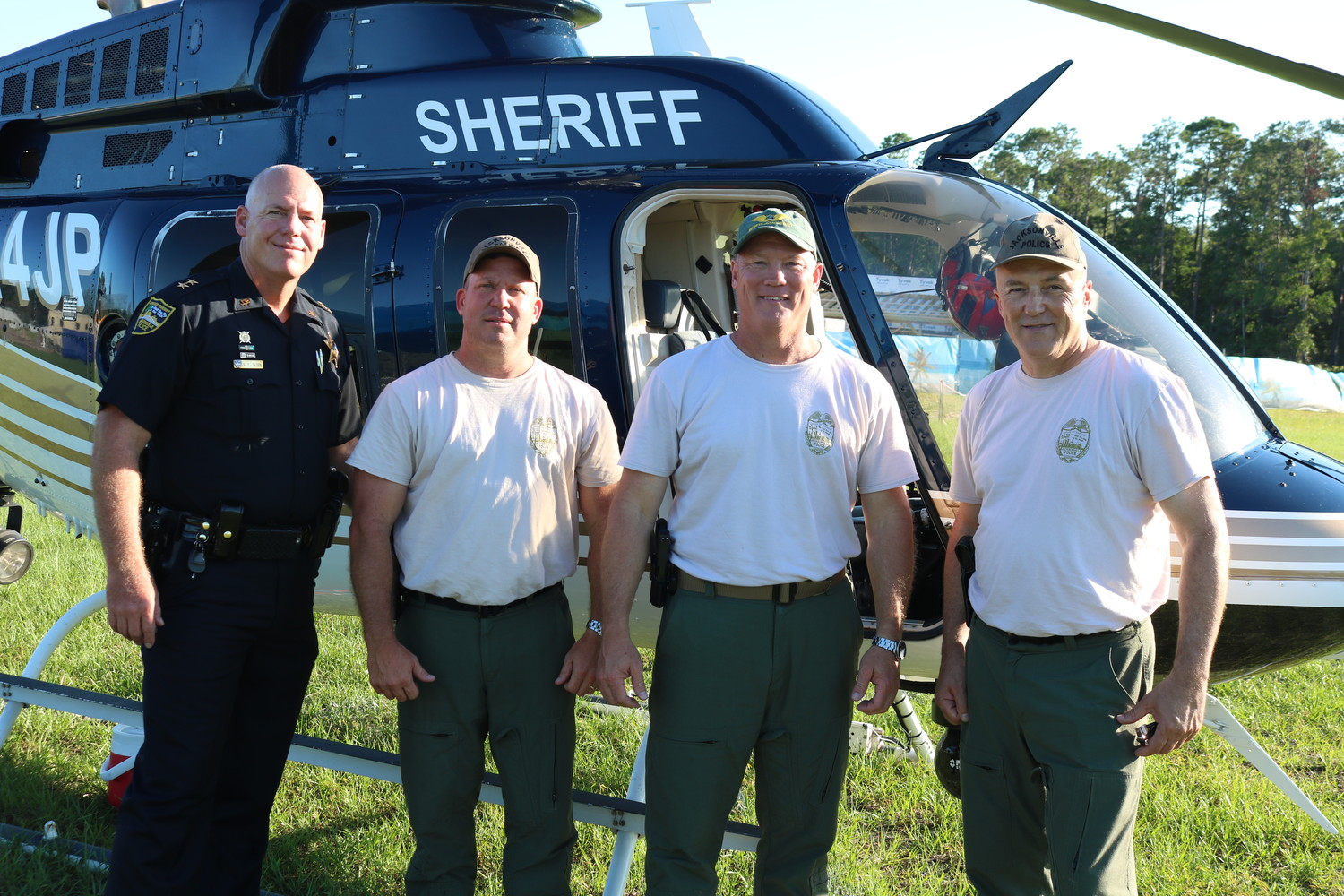 Don Tuten, Mark Newman, Carl Oder and Louis Ferreira of the Jacksonville Sheriff's Office gather in front of a helicopter at Nocatee's Community Resource Day on Aug. 7.