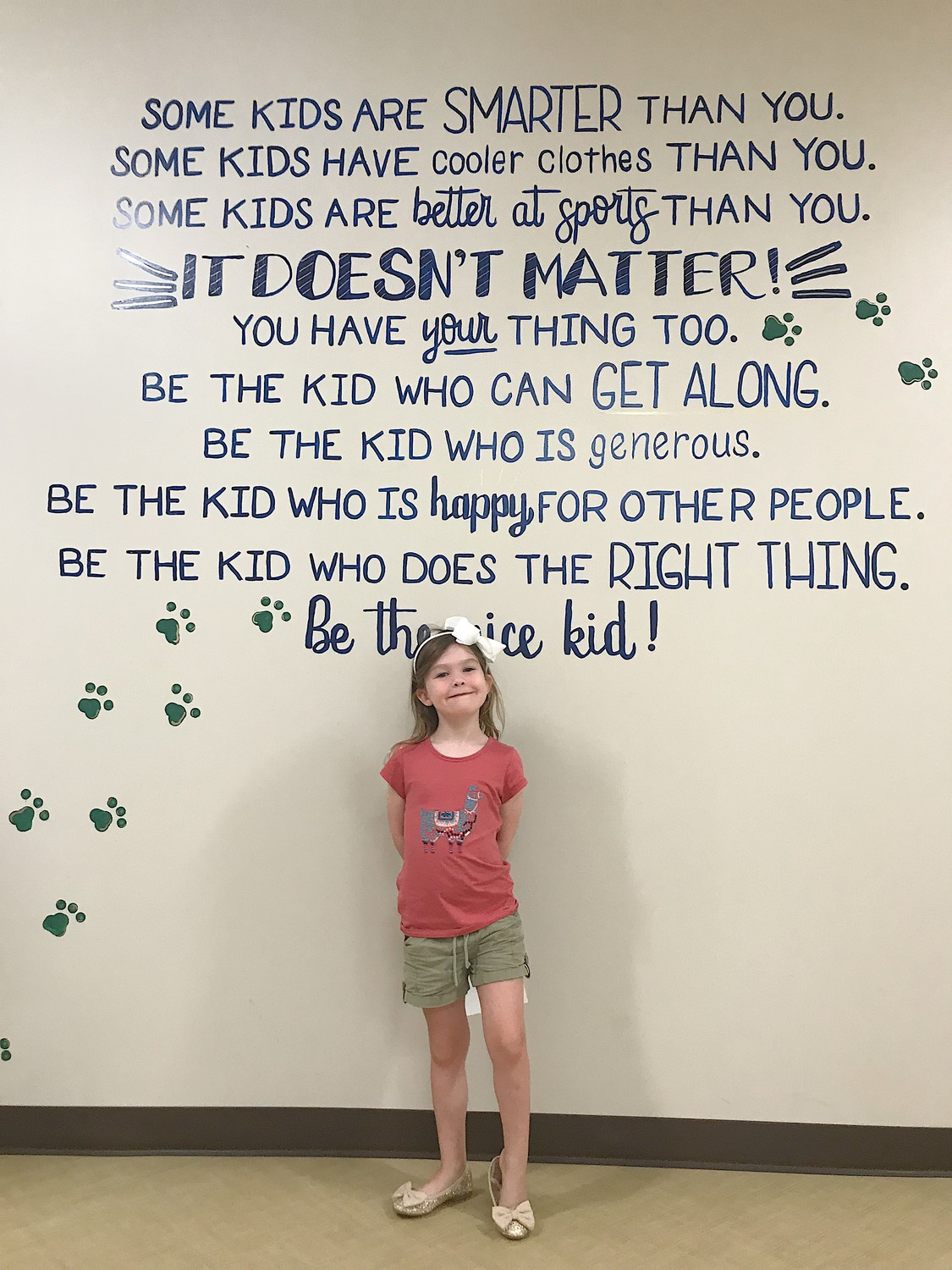 Kindergartner Finnley Strickland poses in front of one of the inspirational art and encouraging messages found throughout the hallways and bathrooms at Palm Valley Academy.