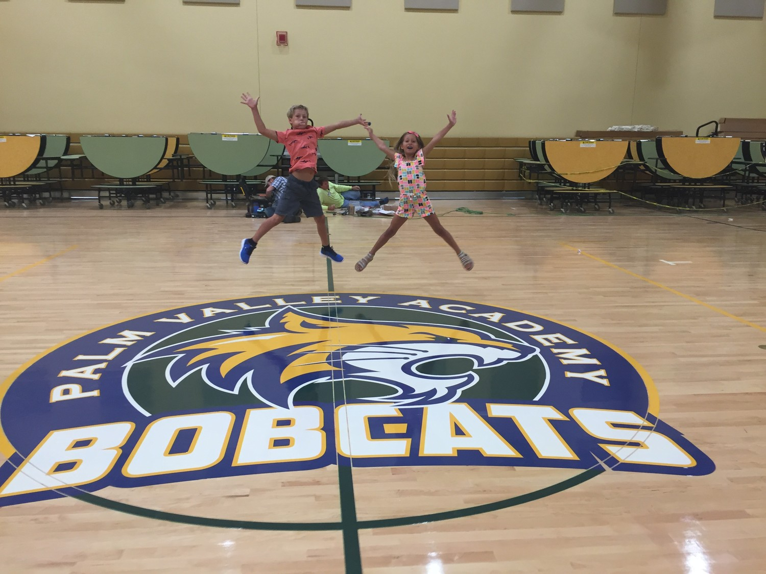 Third-grader Hudson Pennell and first-grader Piper Pennell celebrate their new school in Palm Valley Academy's gymnasium.