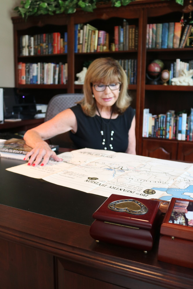 Schmitz looks over a map of the 89th infantry division of the U.S. Army that her father was part of in World War II.